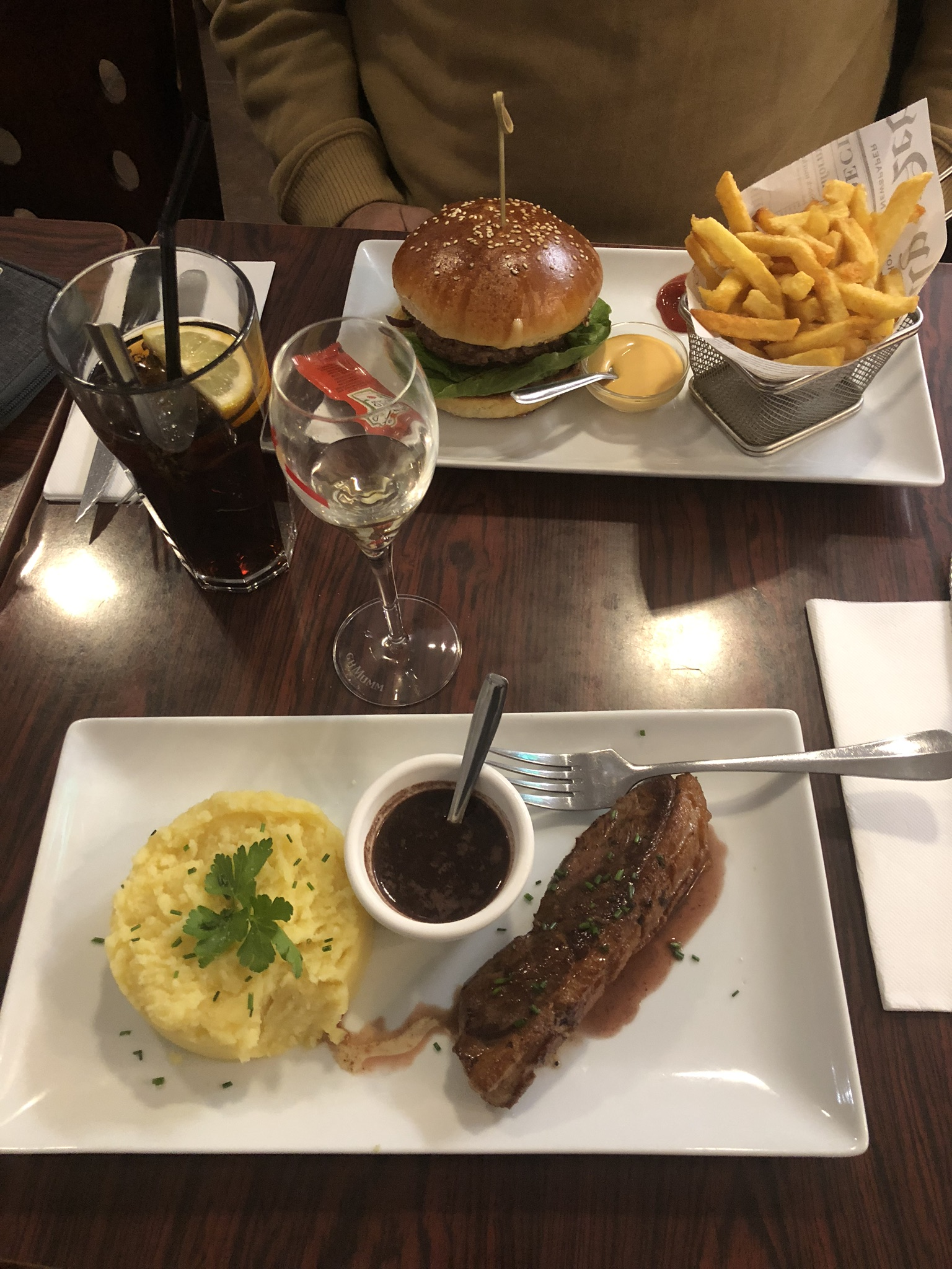 """My husbands """"American"""" cheeseburger and fries. I had lamb and potatoes with an amazing glass of champagne."""