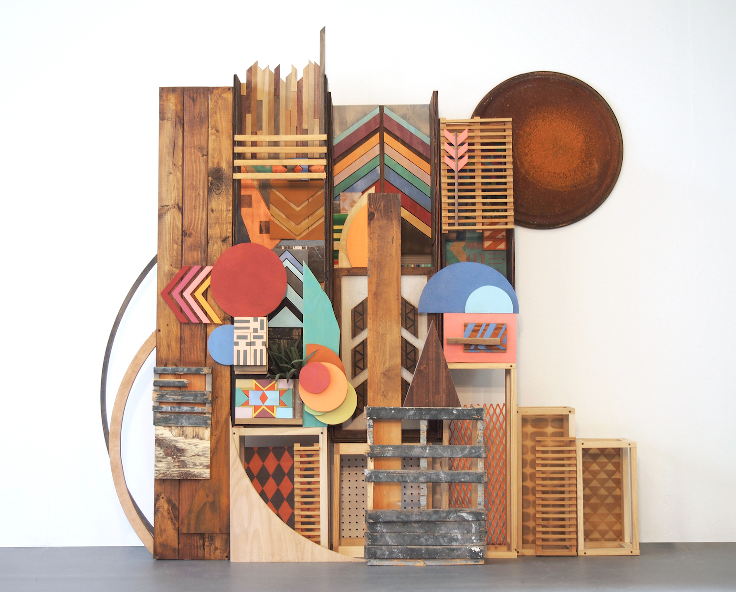 75x70x32 , wood, metal, paper, plastic, found items, woven items, printed fabric, metal drum lid, artificial plant, stain, acrylic paint, 75 x 70 x 32 inches