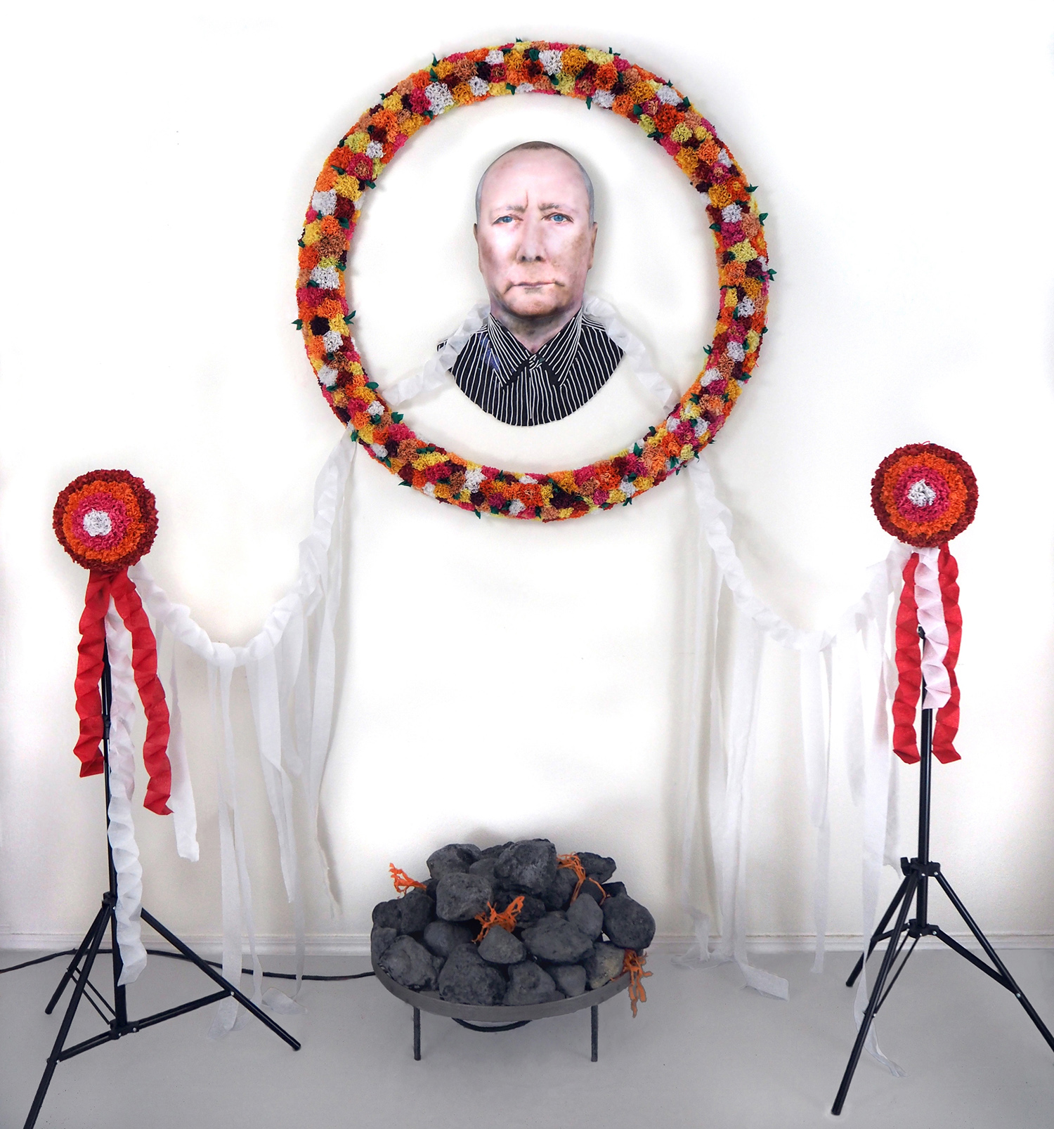 Carrie Fonder,  Portrait of an Artist as a Dead Man , 2016, Urethane foam, tissue paper, streamers, steel, yarn, airbrushed acrylic, 80 x 85 x 46 inches  This mixed media sculptural installation features an airbrushed acrylic portrait of artist Mike Kelley. A tissue paper wreath, streamers, and urethane foam rocks surround the portrait and are activated by a concealed fan.
