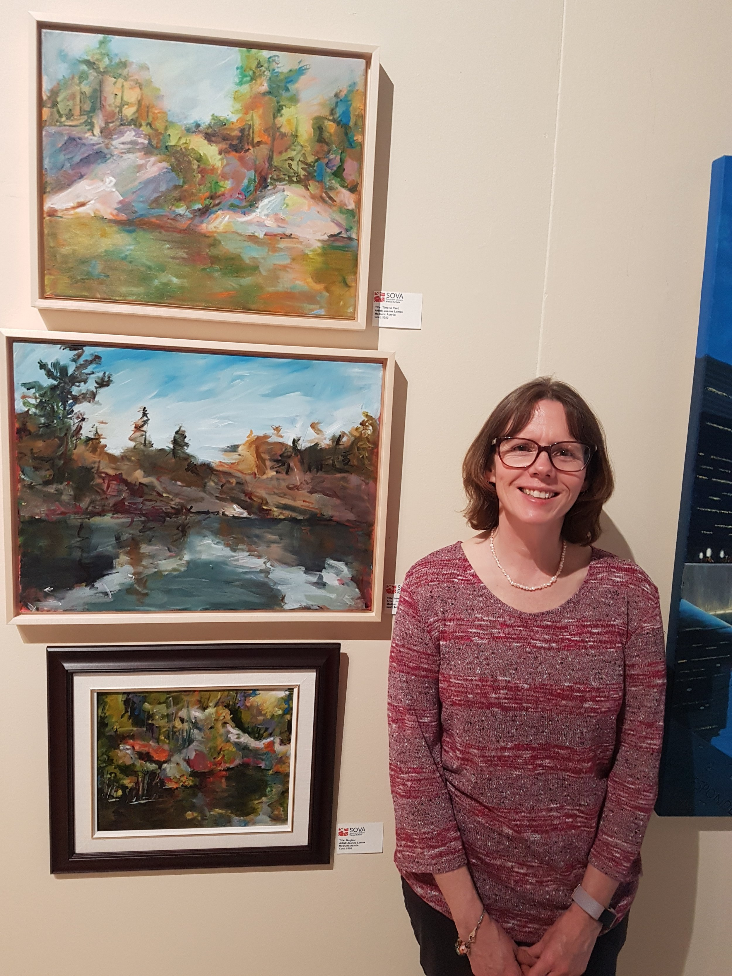 - Here you see Artist Joanne Lomas with her artwork at the Joseph D. Carrier Gallery.