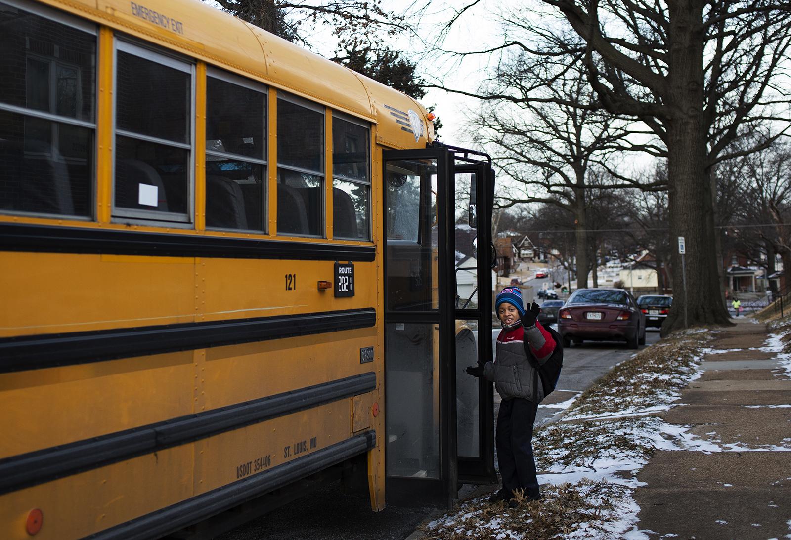 Johnny waves goodbye to his mom, Keyanna, as he boards the bus to school. CAROLINA HIDALGO   ST. LOUIS PUBLIC RADIO