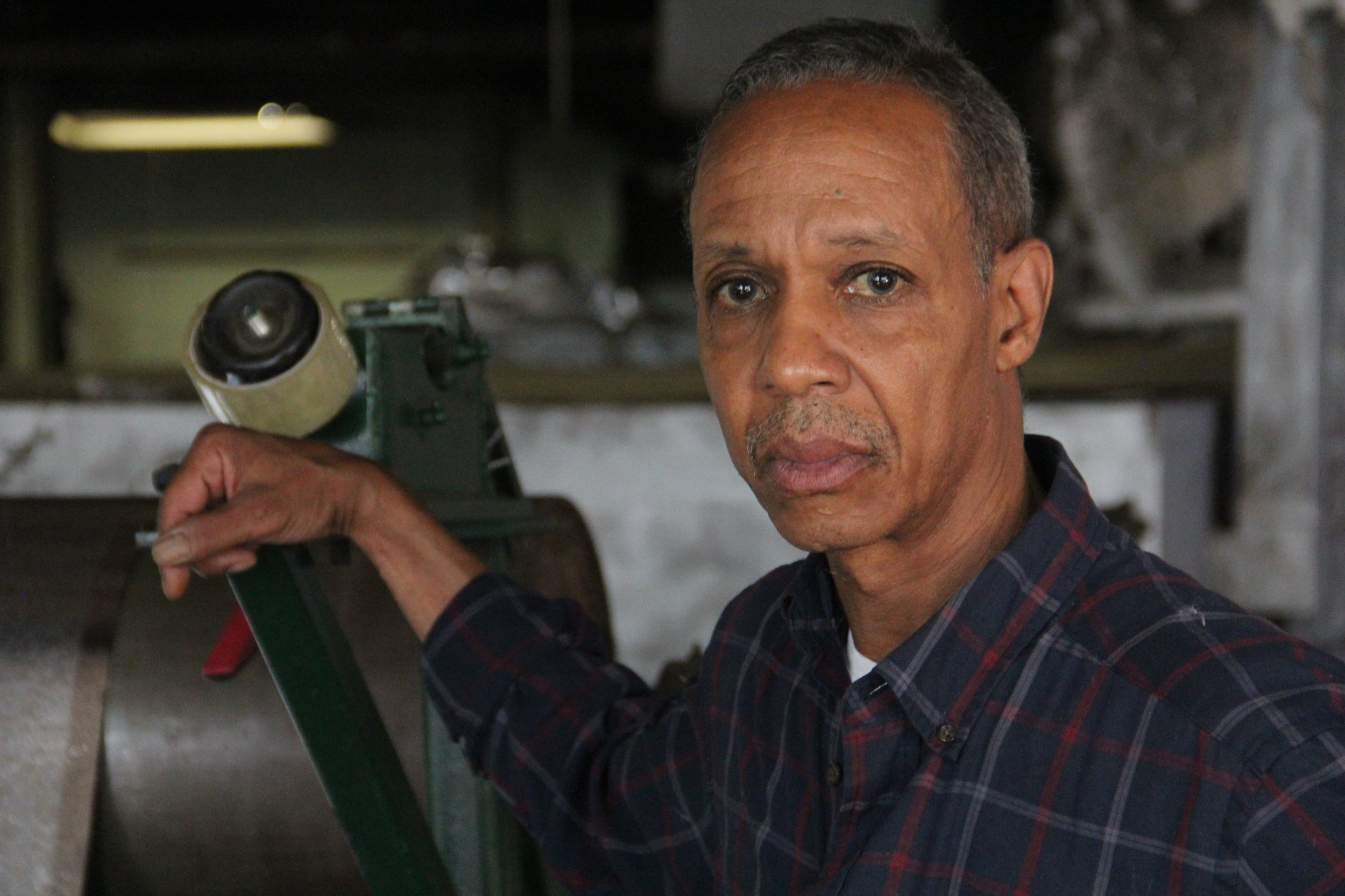 Greg Gibson stands next to machinery in the north St. Louis factory where he works. (Tim Lloyd, We Live Here)