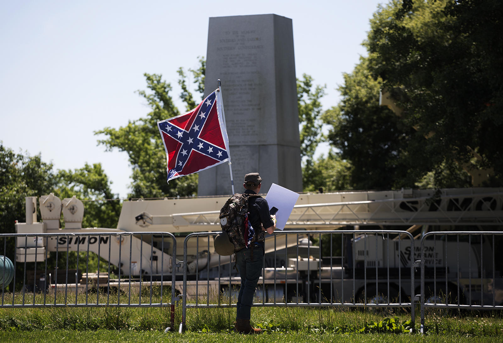 Brendan Koch, of Arnold, Missouri, looks at the Confederate Memorial after crews removed the top of it Thursday morning. (Carolina Hidalgo, St. Louis Public Radio)
