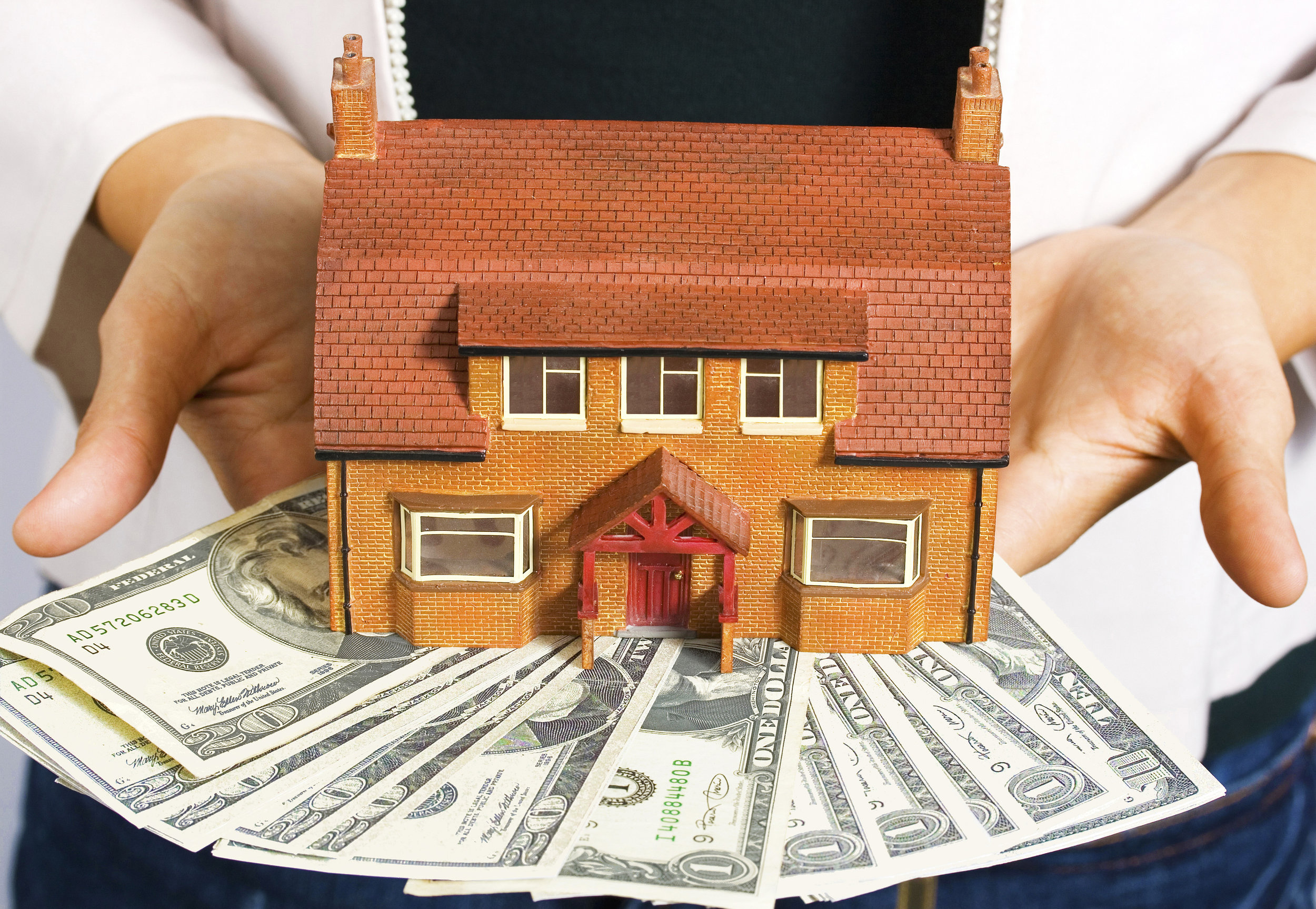 a-person-holding-a-miniature-house-and-some-dollar-bills_f17FkBDO.jpg