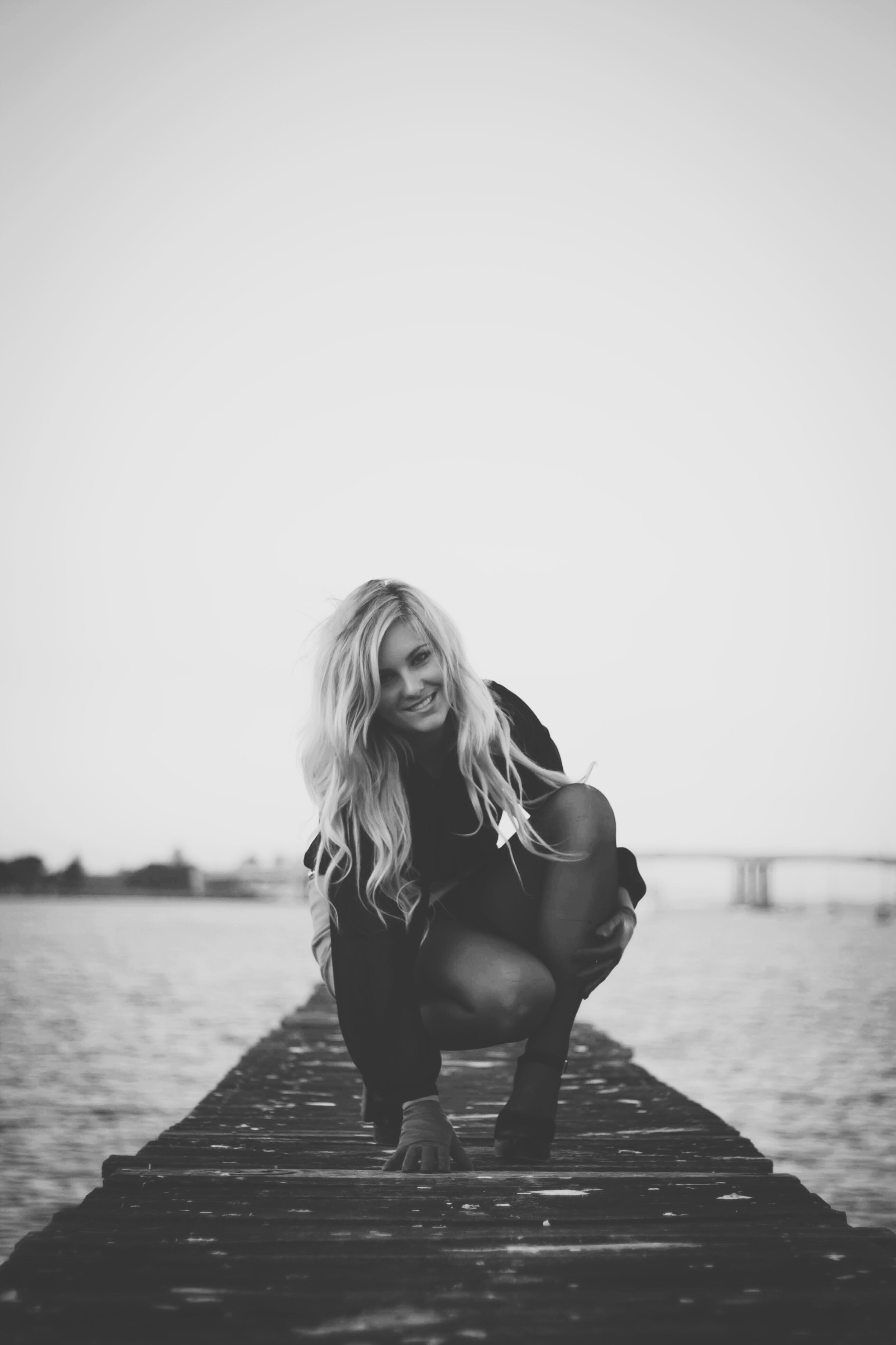 young girl sitting on wharf