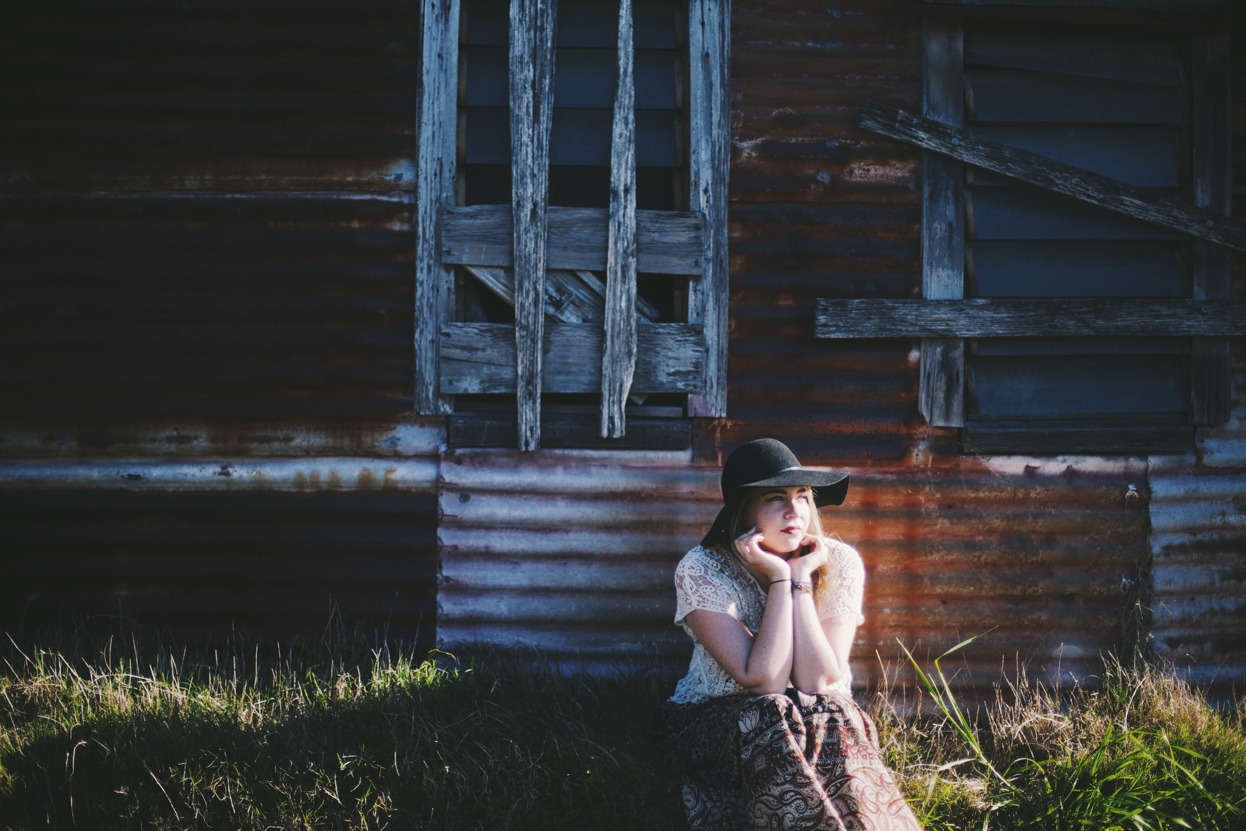 woman sitting near rustic cottage with golden light