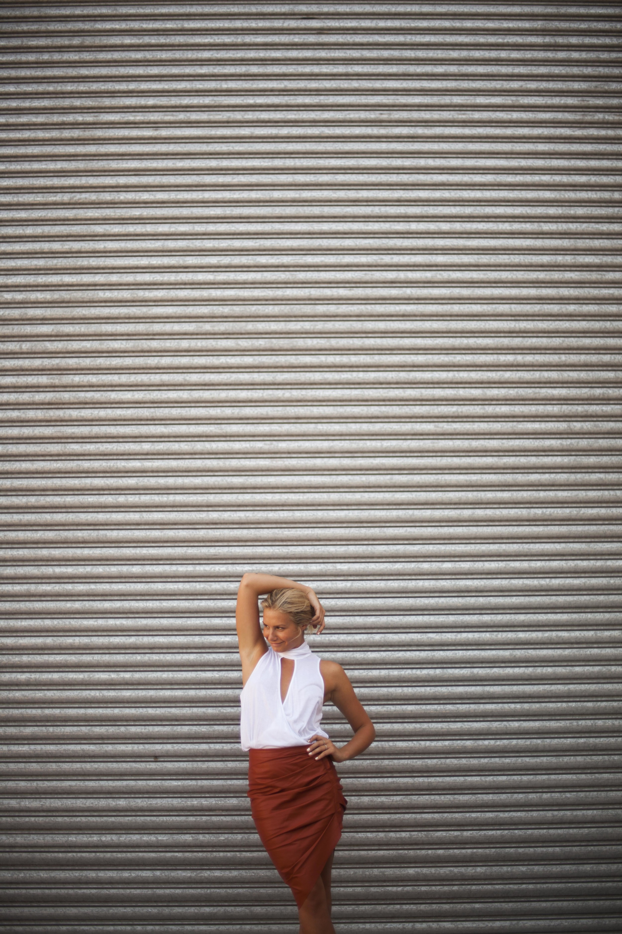 girl standing against corrigated iron wall