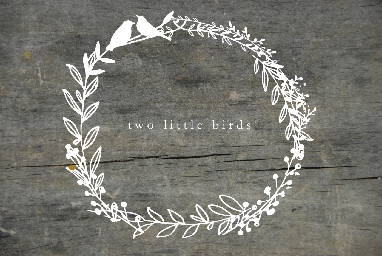 Two little birds logo white lettering surrounded by circle of florals