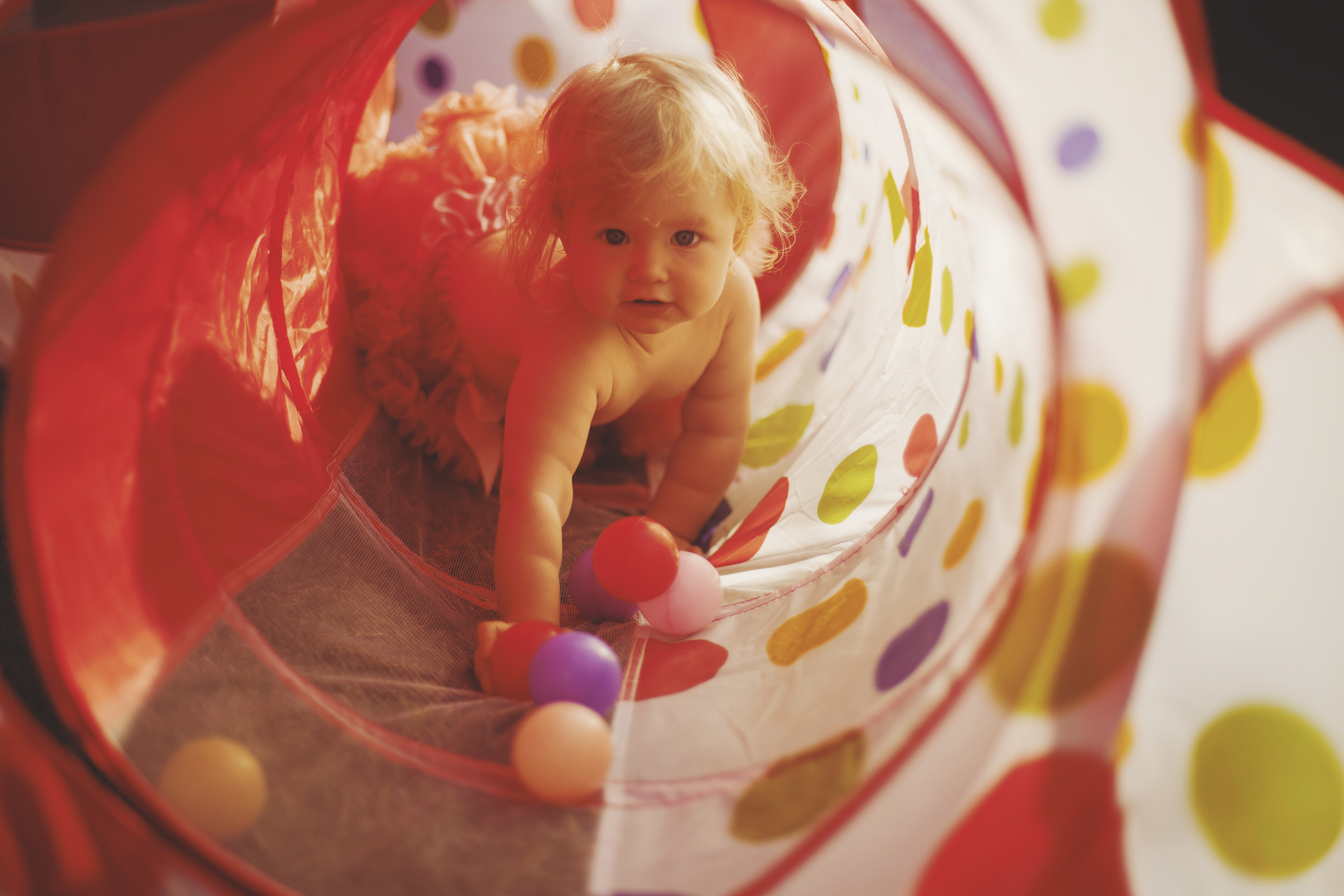 Baby crawling through colourful tunnel