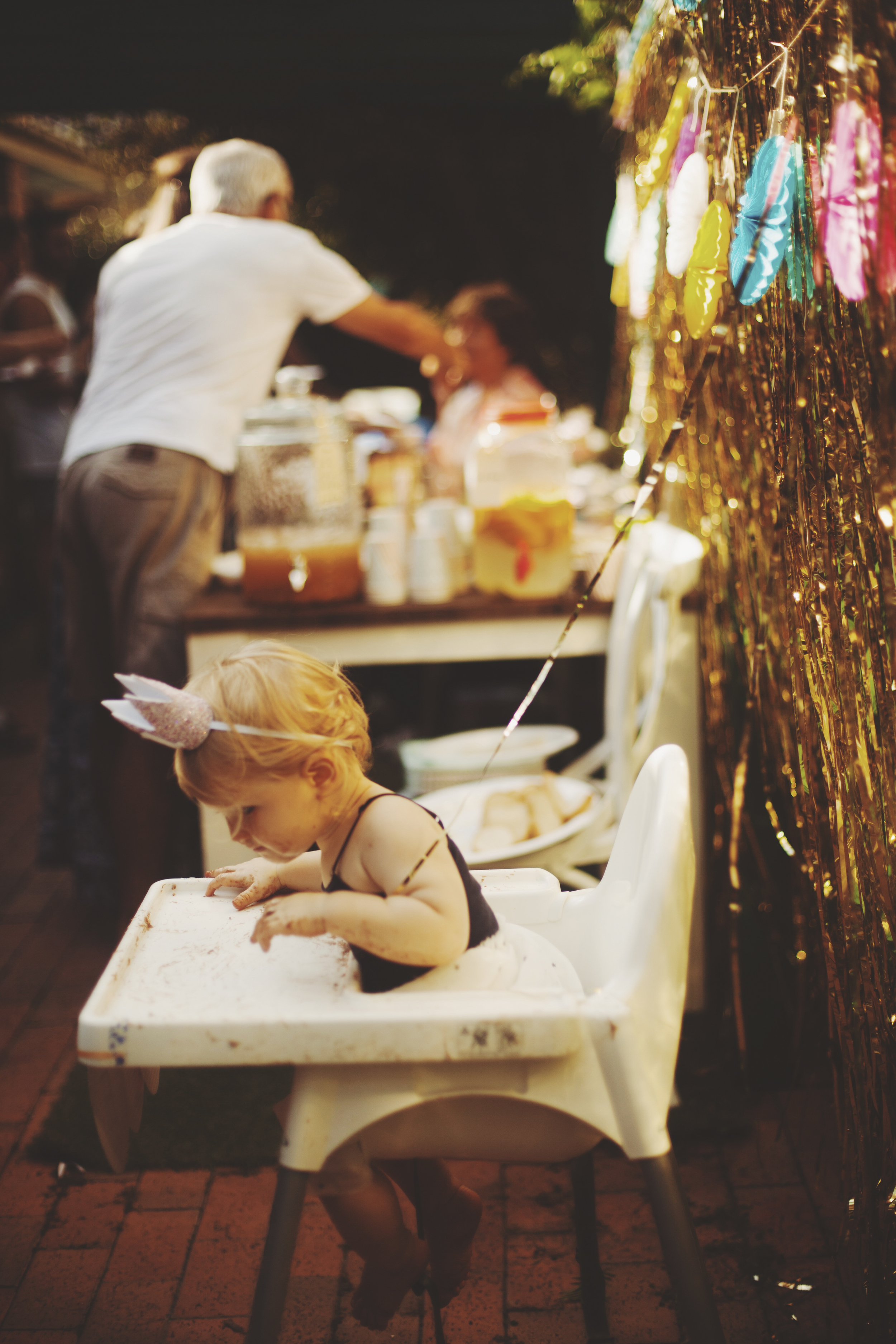 baby in high chair wearing party hat