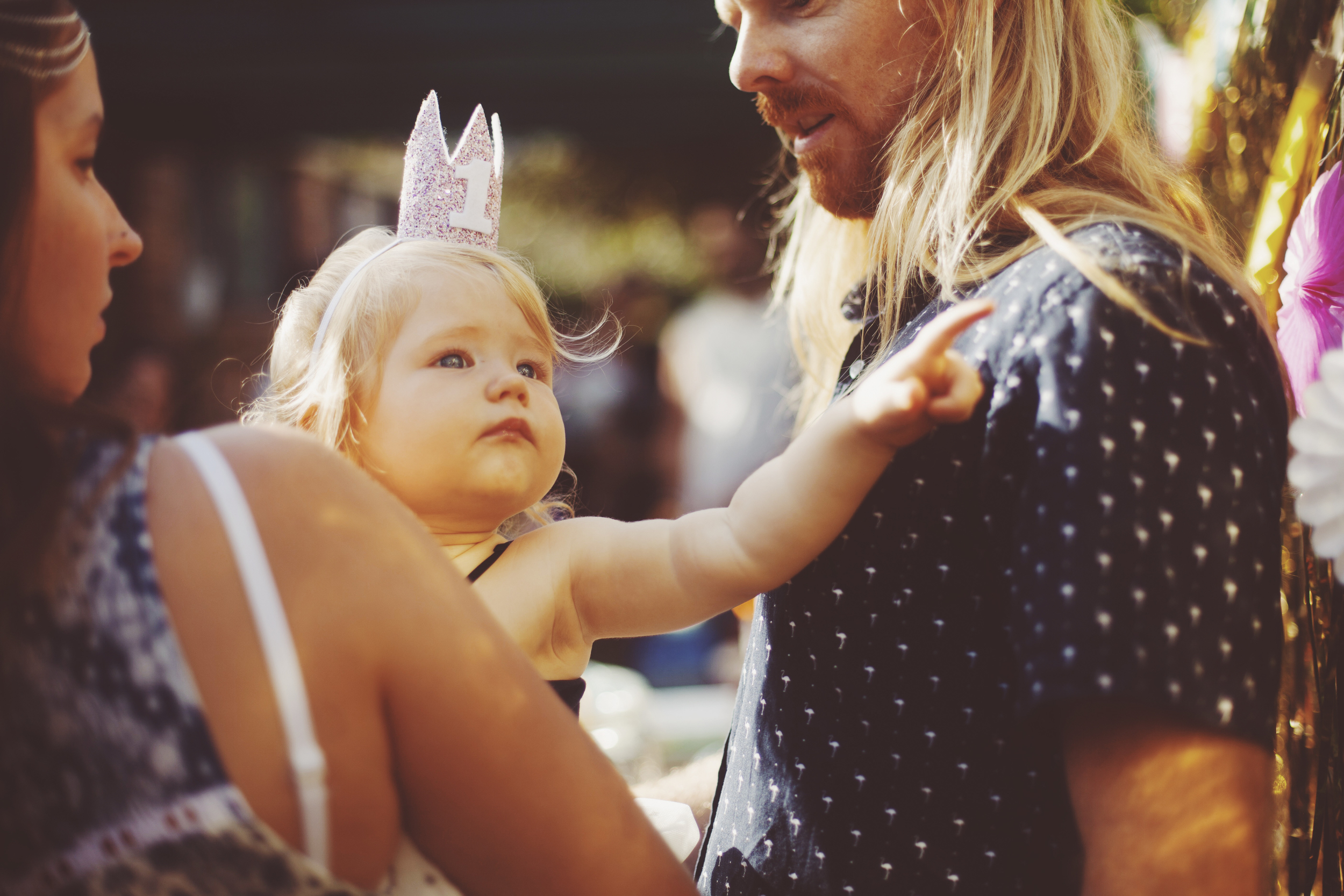 baby reaching for dad at first birthday party