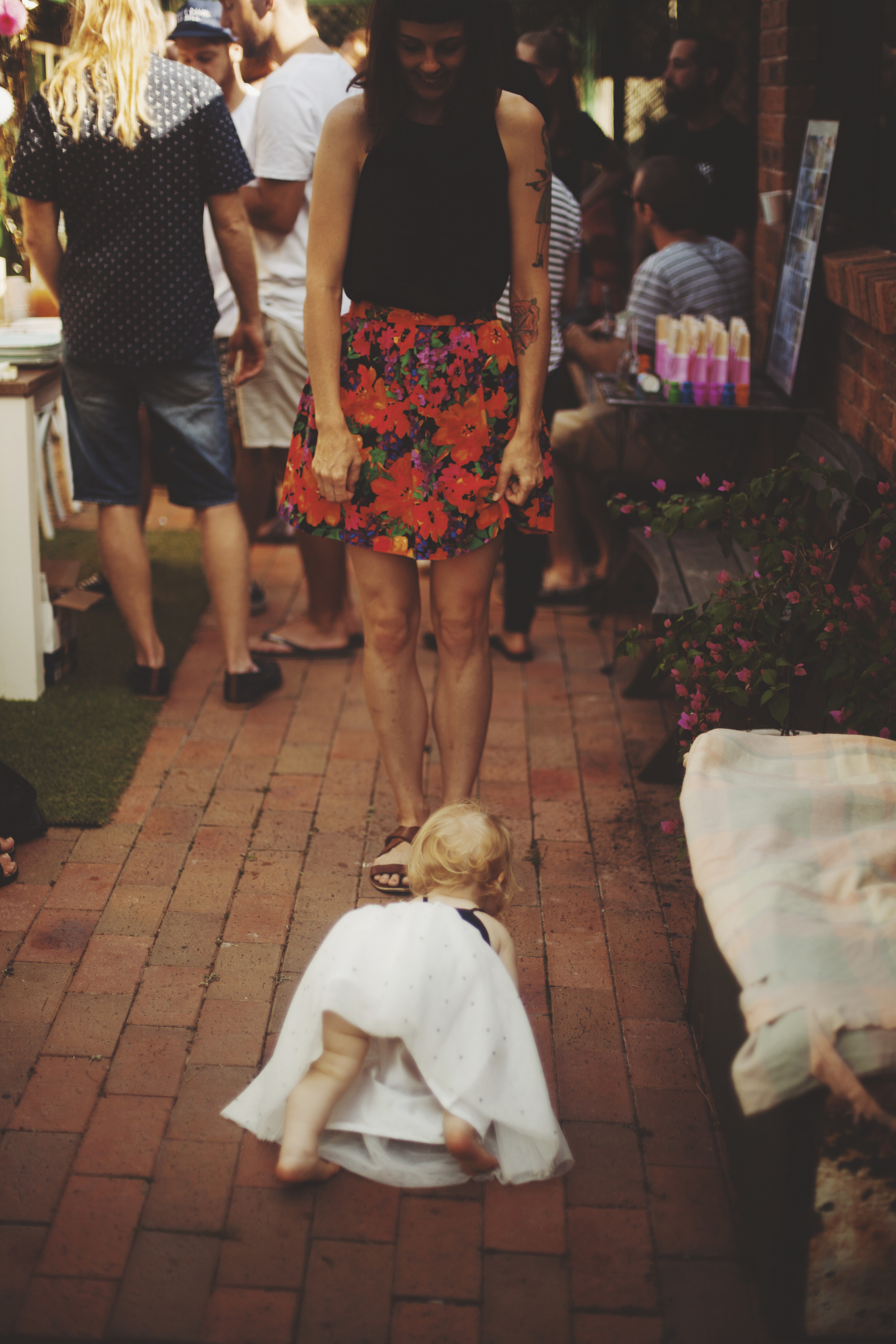 baby crawling on floor surrounded by people at first birthday party