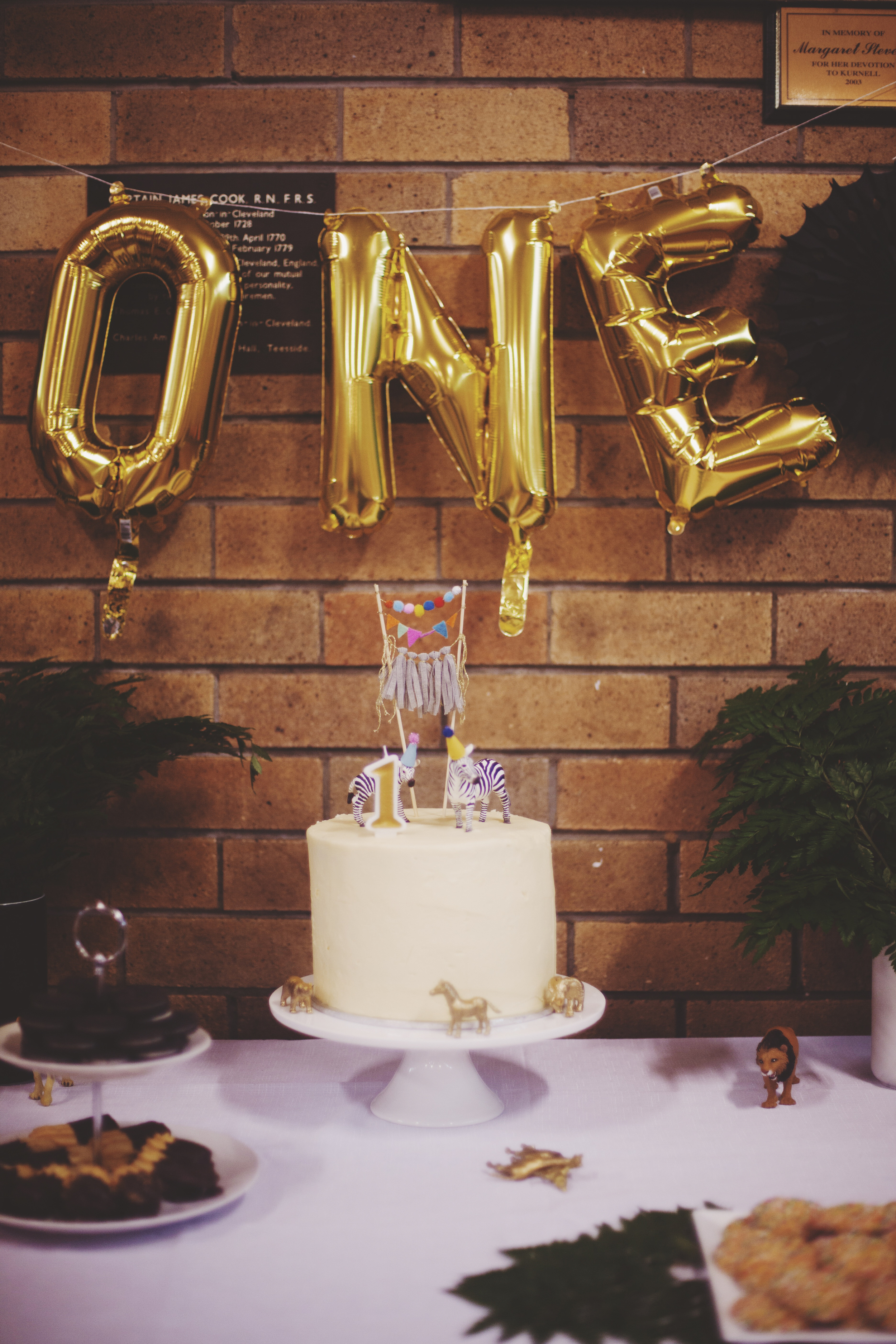 birthday cake with gold balloons above that spell the word one