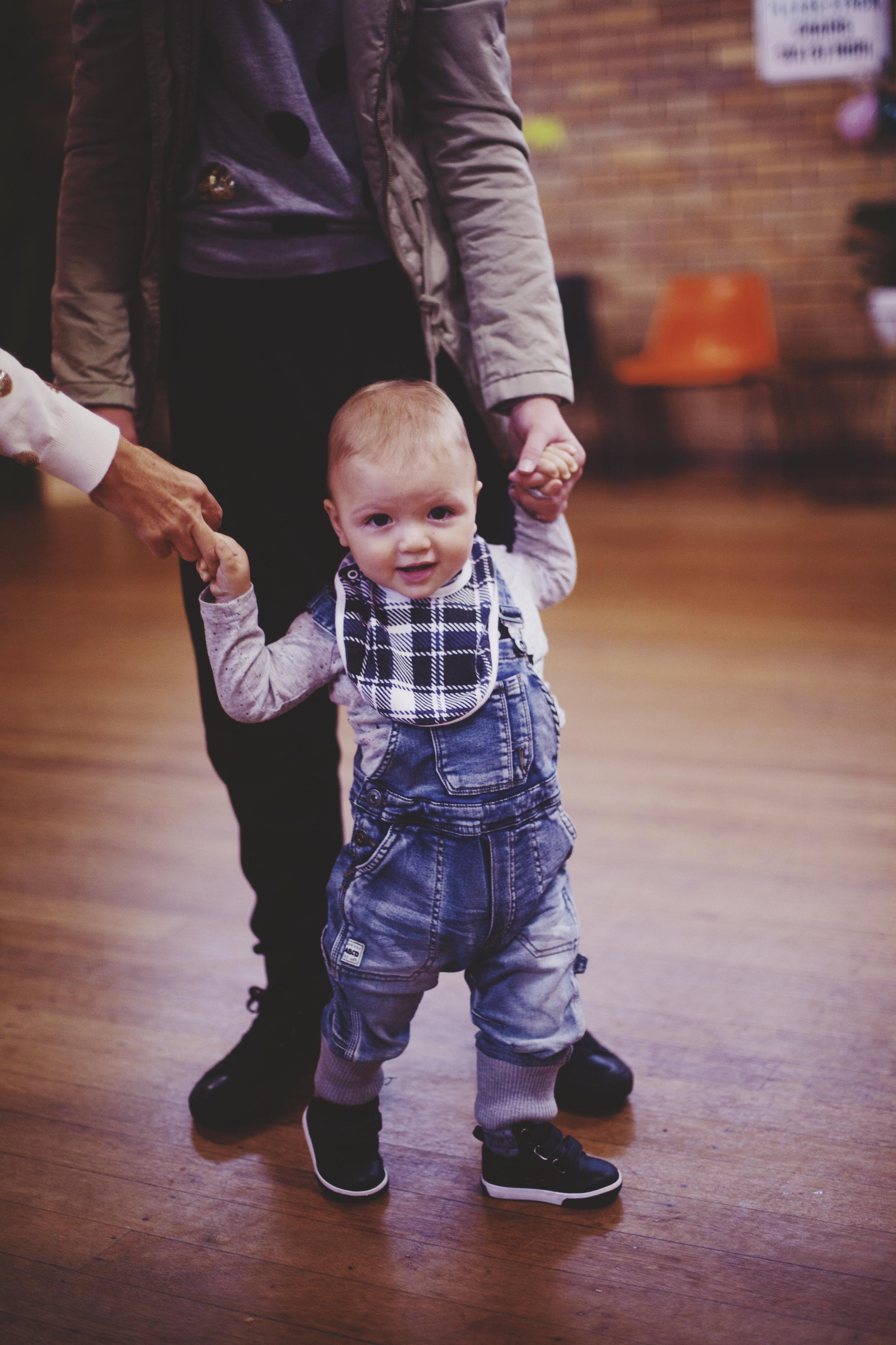 young boy standing on floor wearing denim overalls