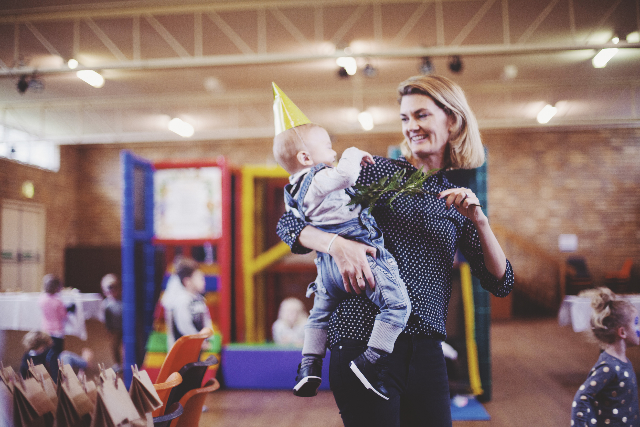 woman holding baby wearing lime green party hat