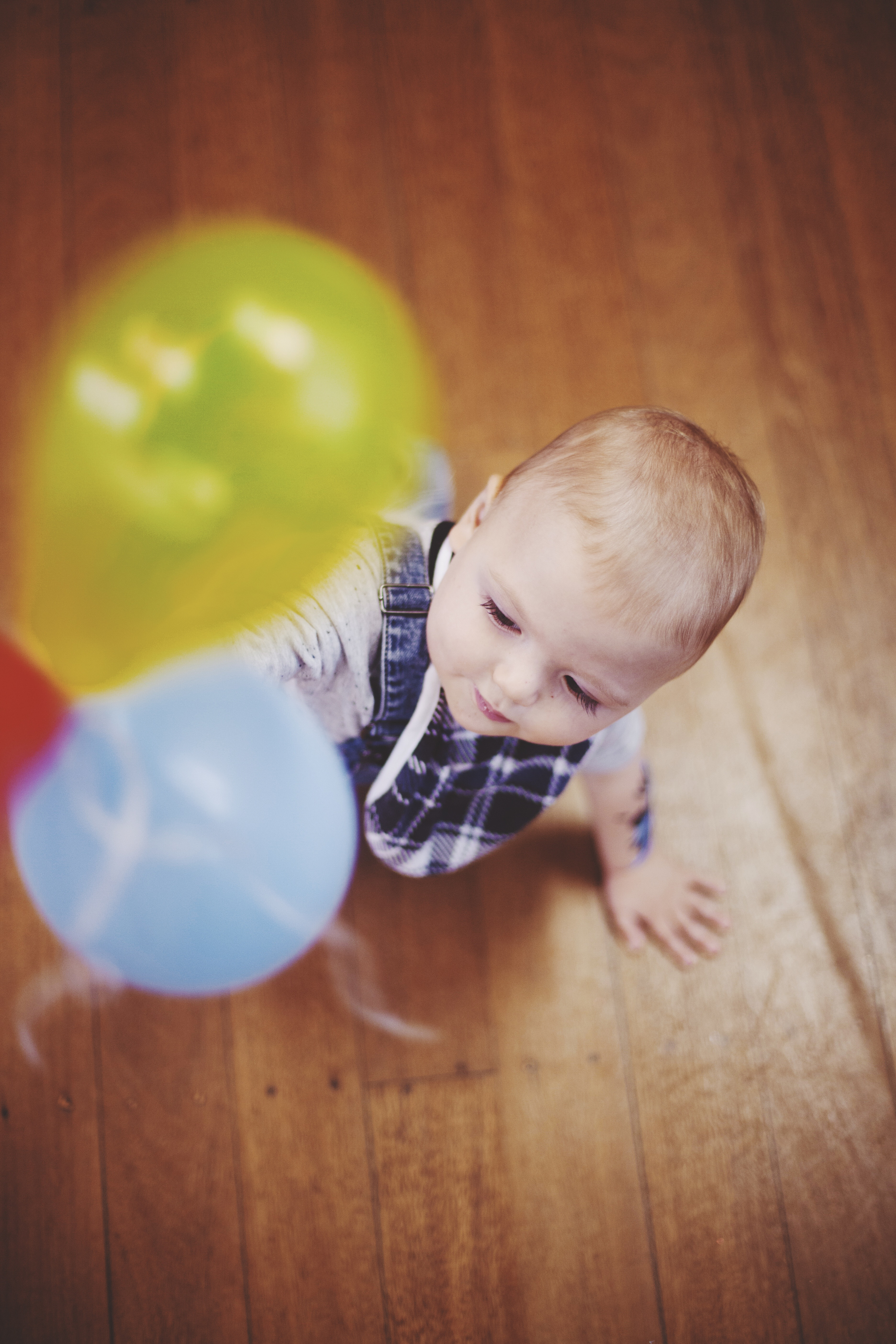 baby playing with two coloured balloons