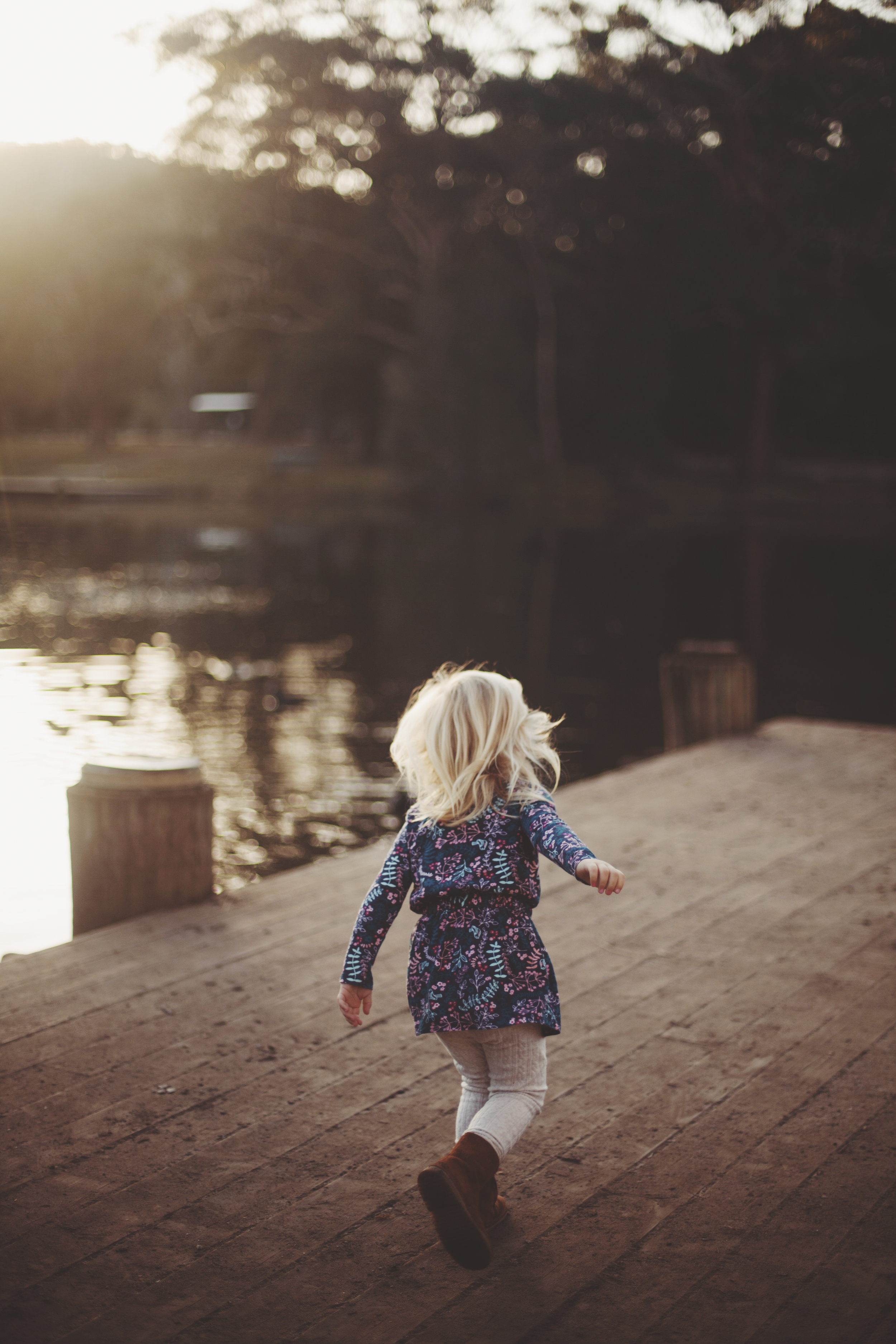 young girl running along waters edge