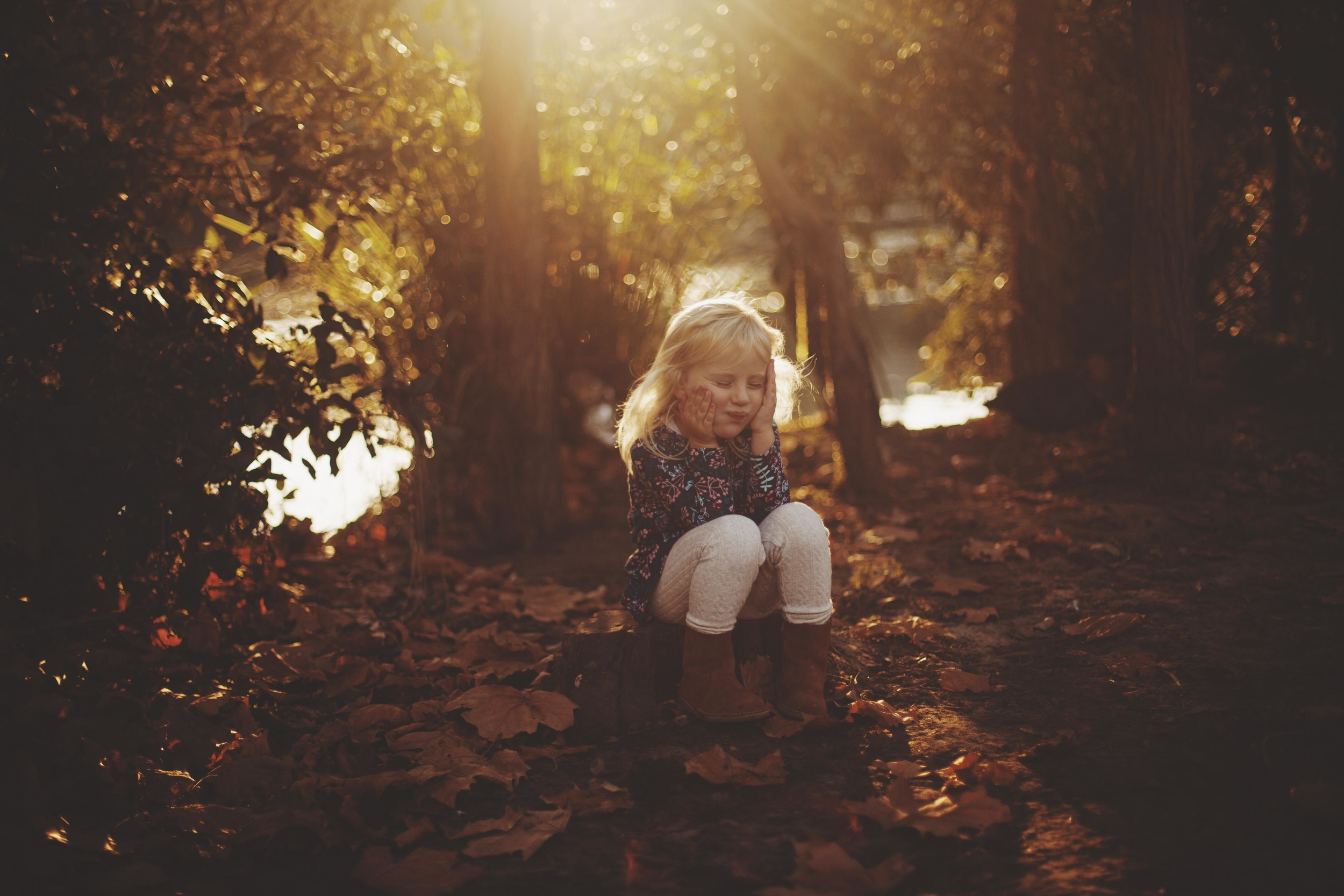 young girl sitting amongst the autumn leaves at sunset