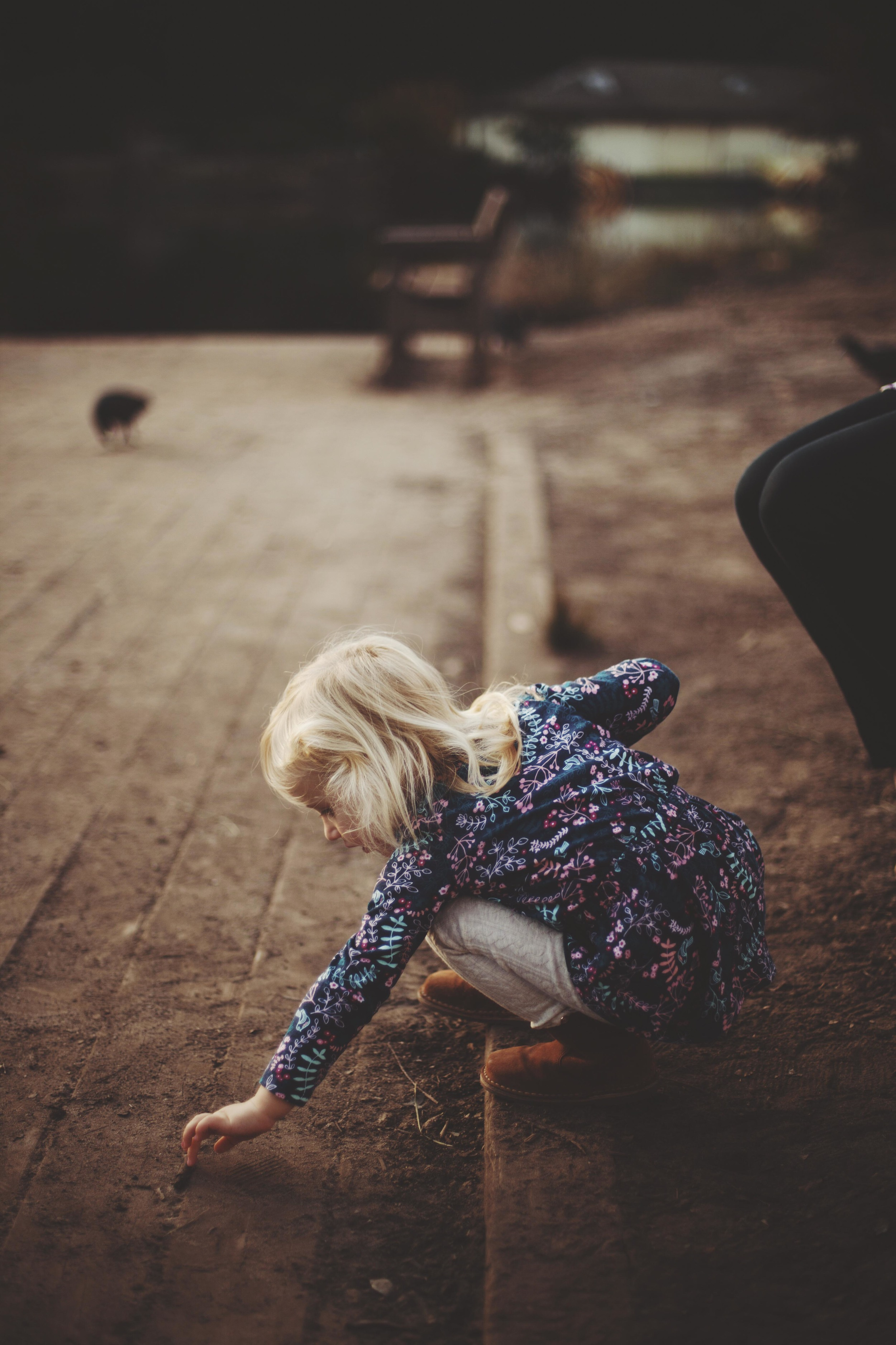 young girl bending to pick up something from the ground