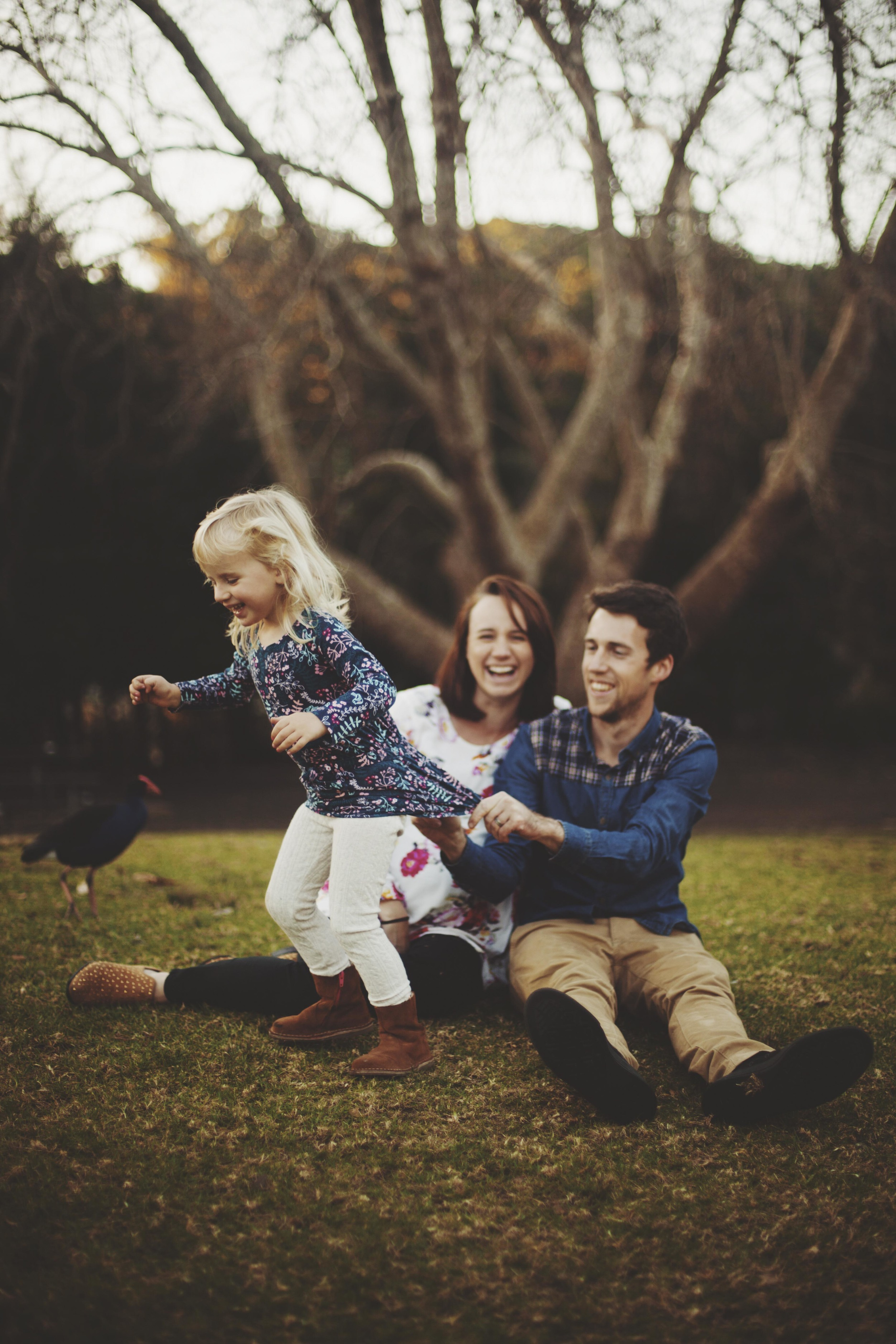 family sitting on grass daughter trying to run away