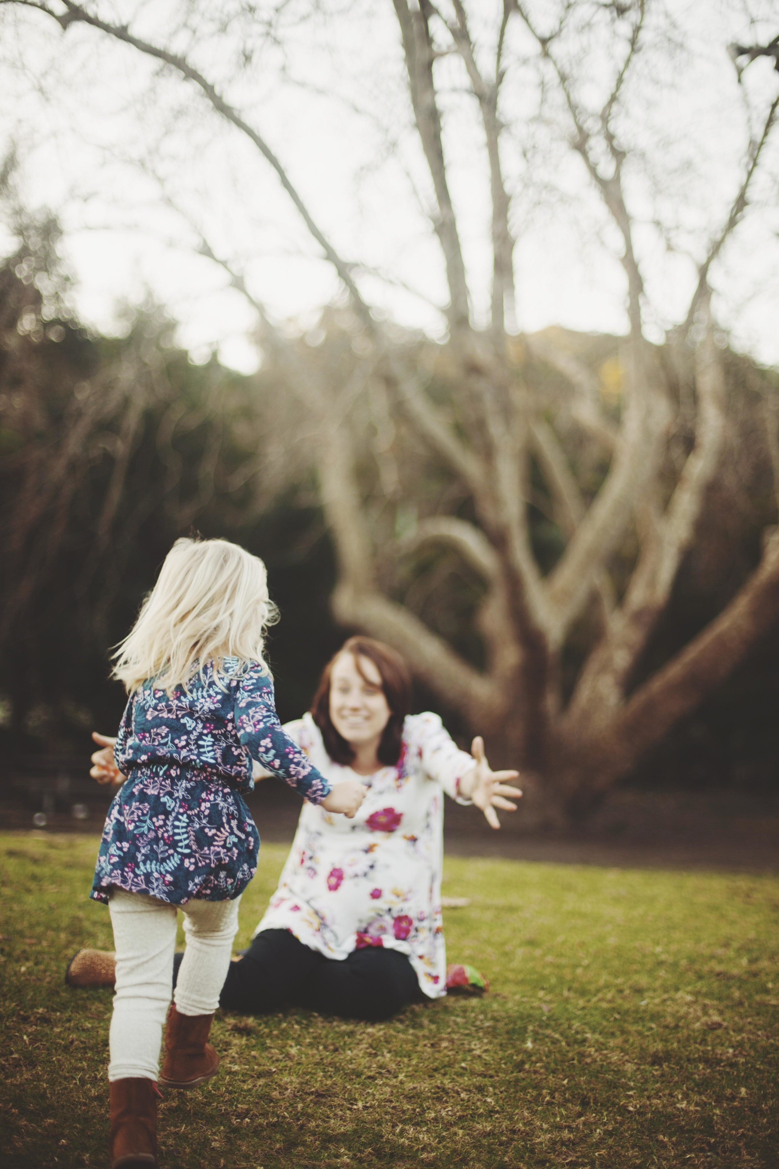 mother and daughter laughing on grass