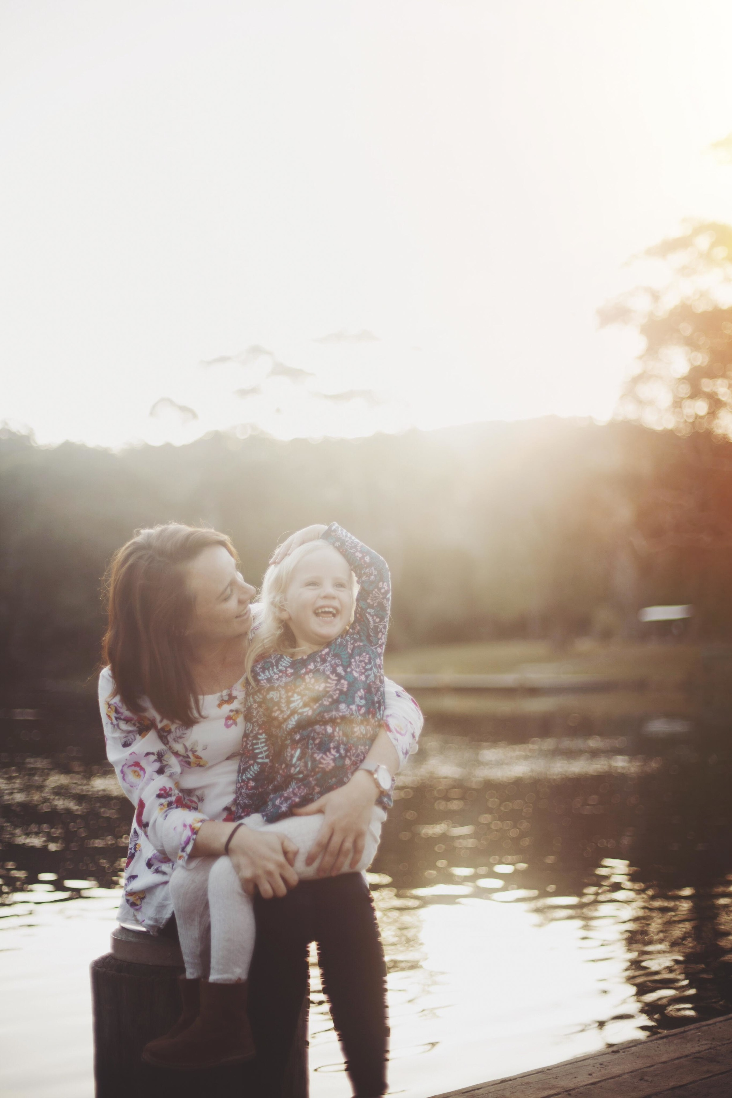 mother and daughter laughing together at sunset by the water