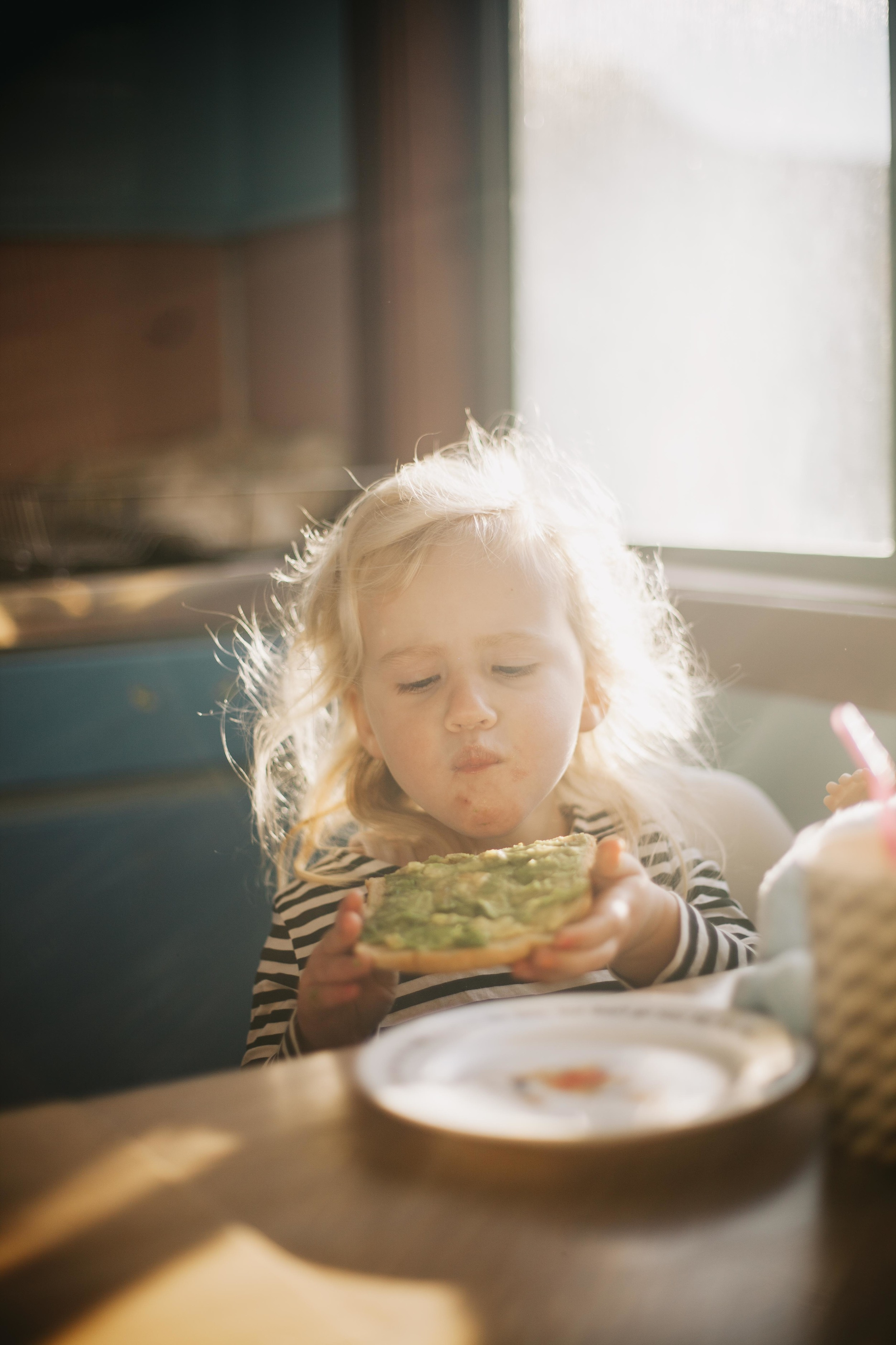 young girl sitting at kitchen table eating avocado toast for breakfast