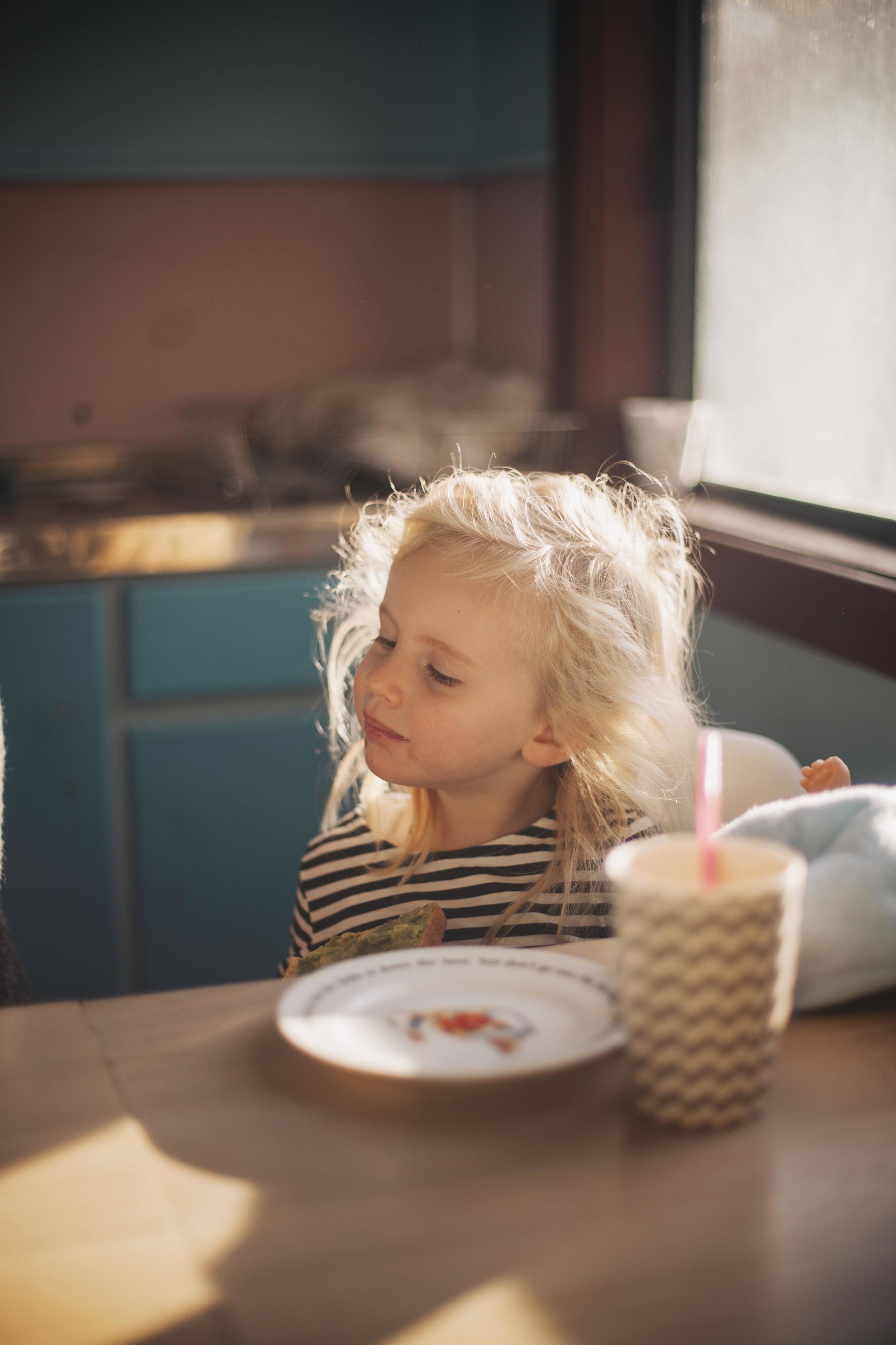 young girl eating toast for breakfast sitting at kitchen table