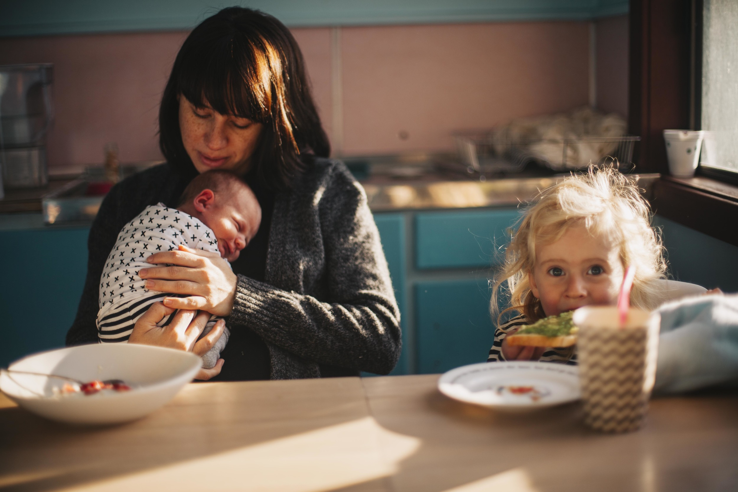 mother holding newborn baby while daughter eats toast at kitchen table