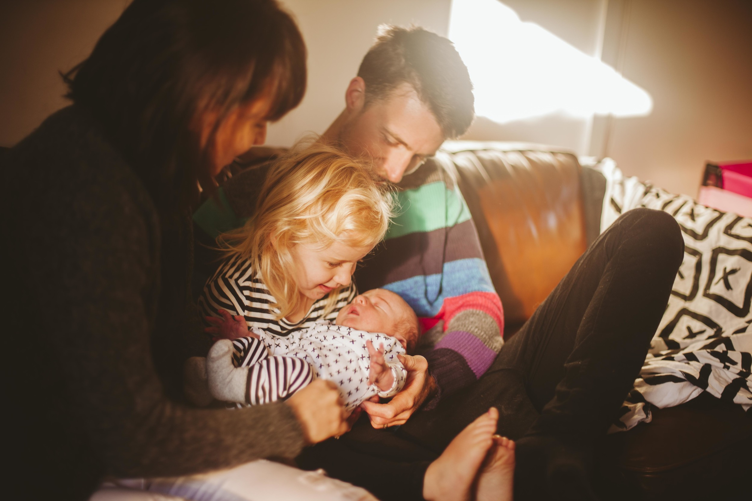 family laughing on couch looking at newborn son