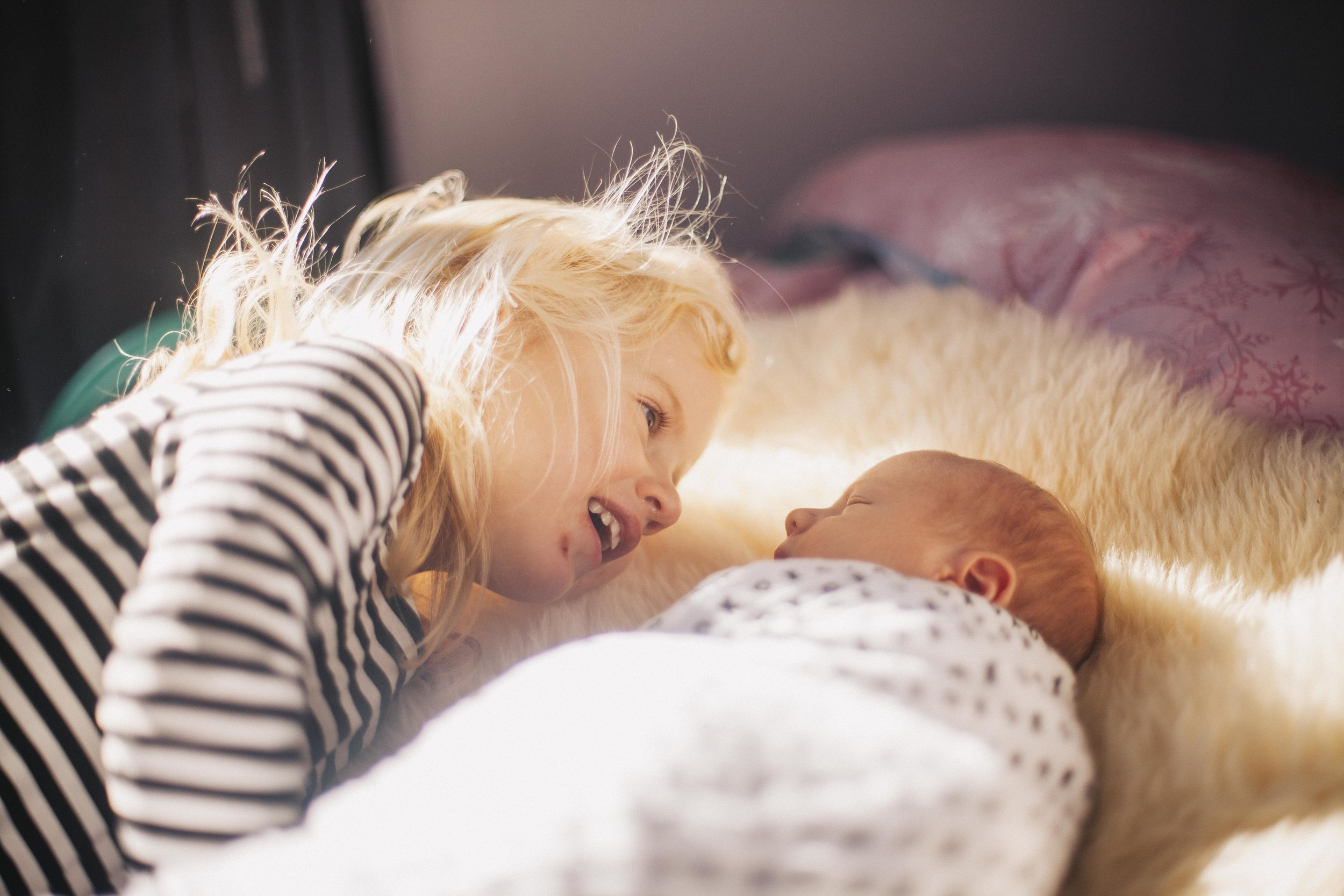 young girl looking at newborn brother