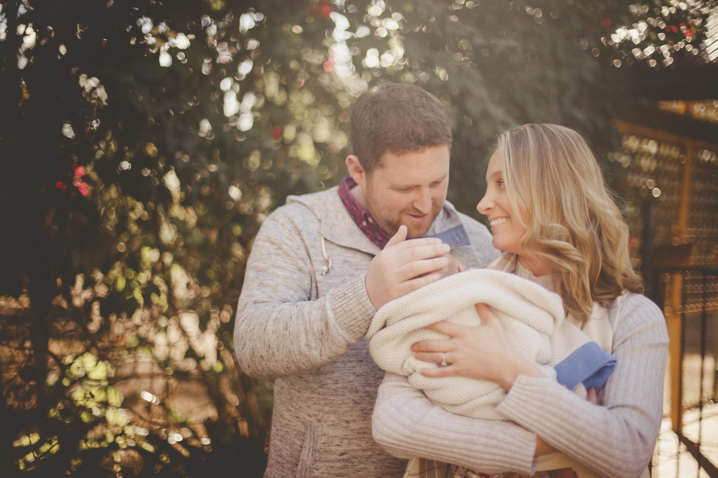 parents smiling at newborn