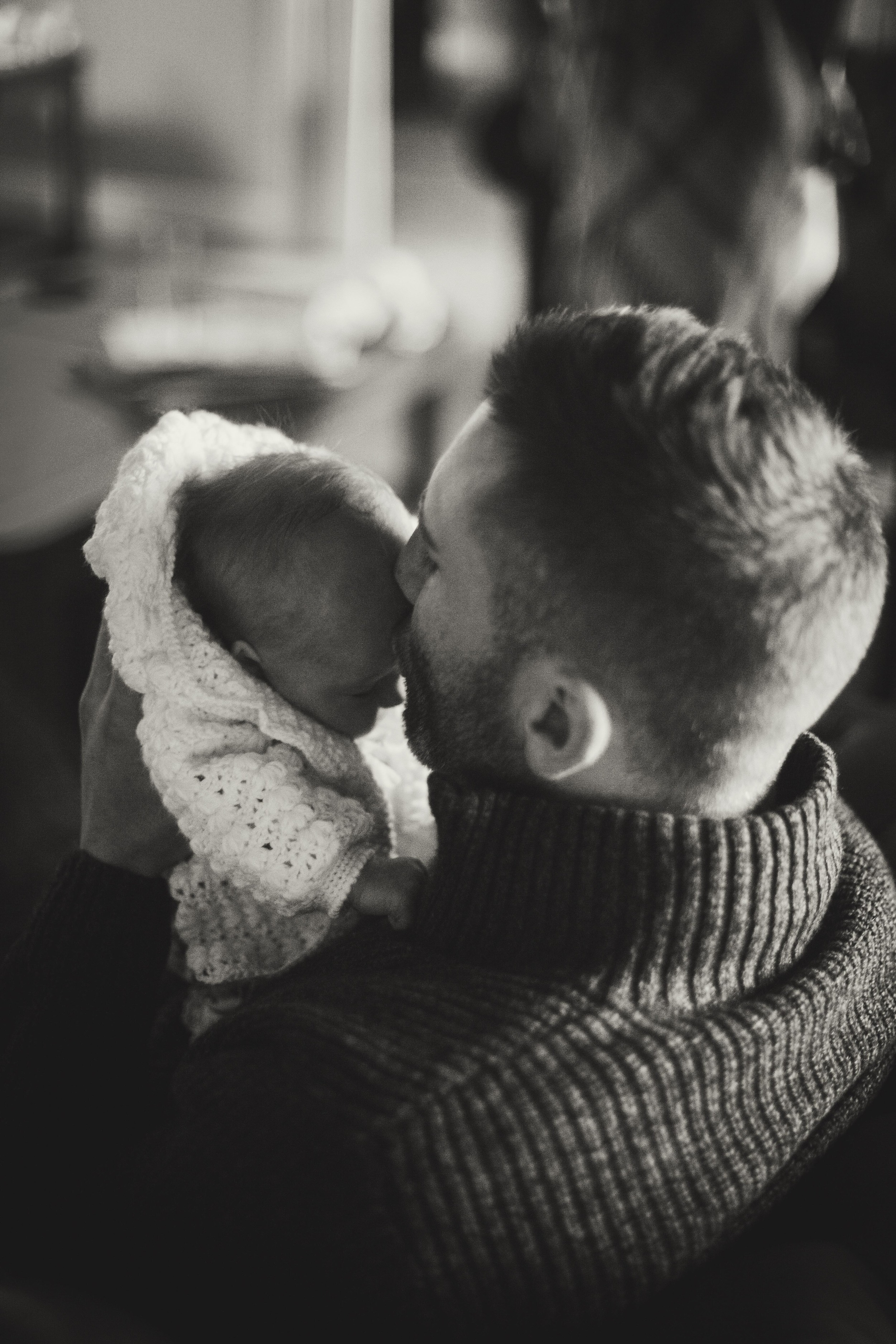 father smelling newborns forehead