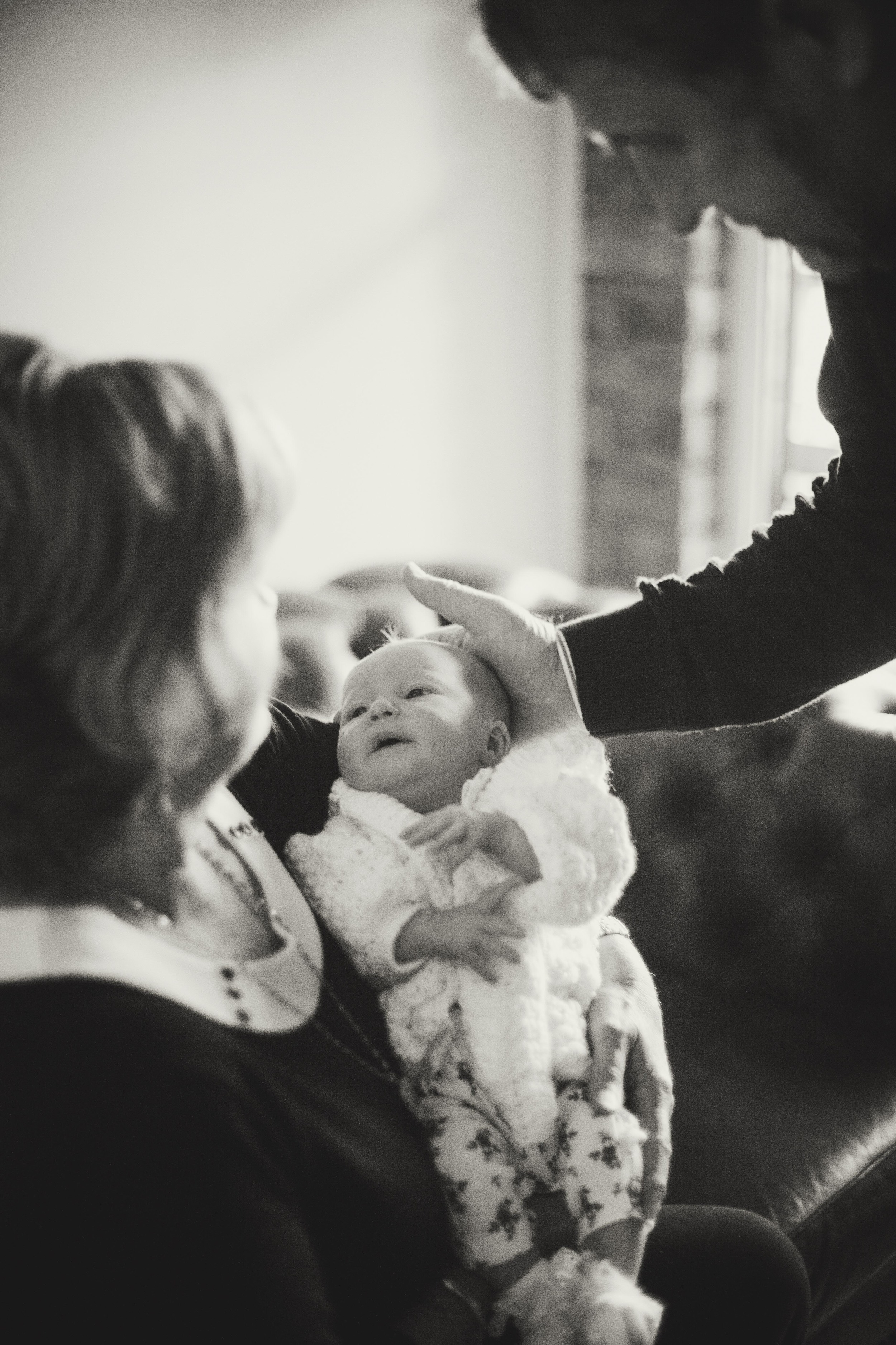 grandparents holding newborn