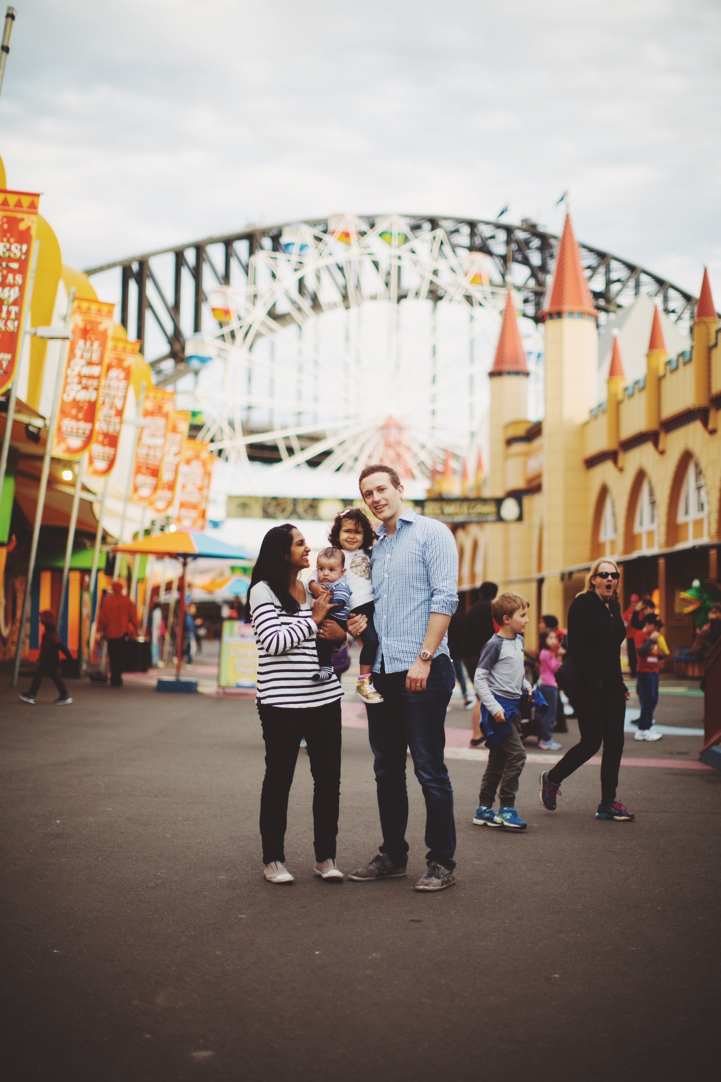 family of four standing in luna park in sydney