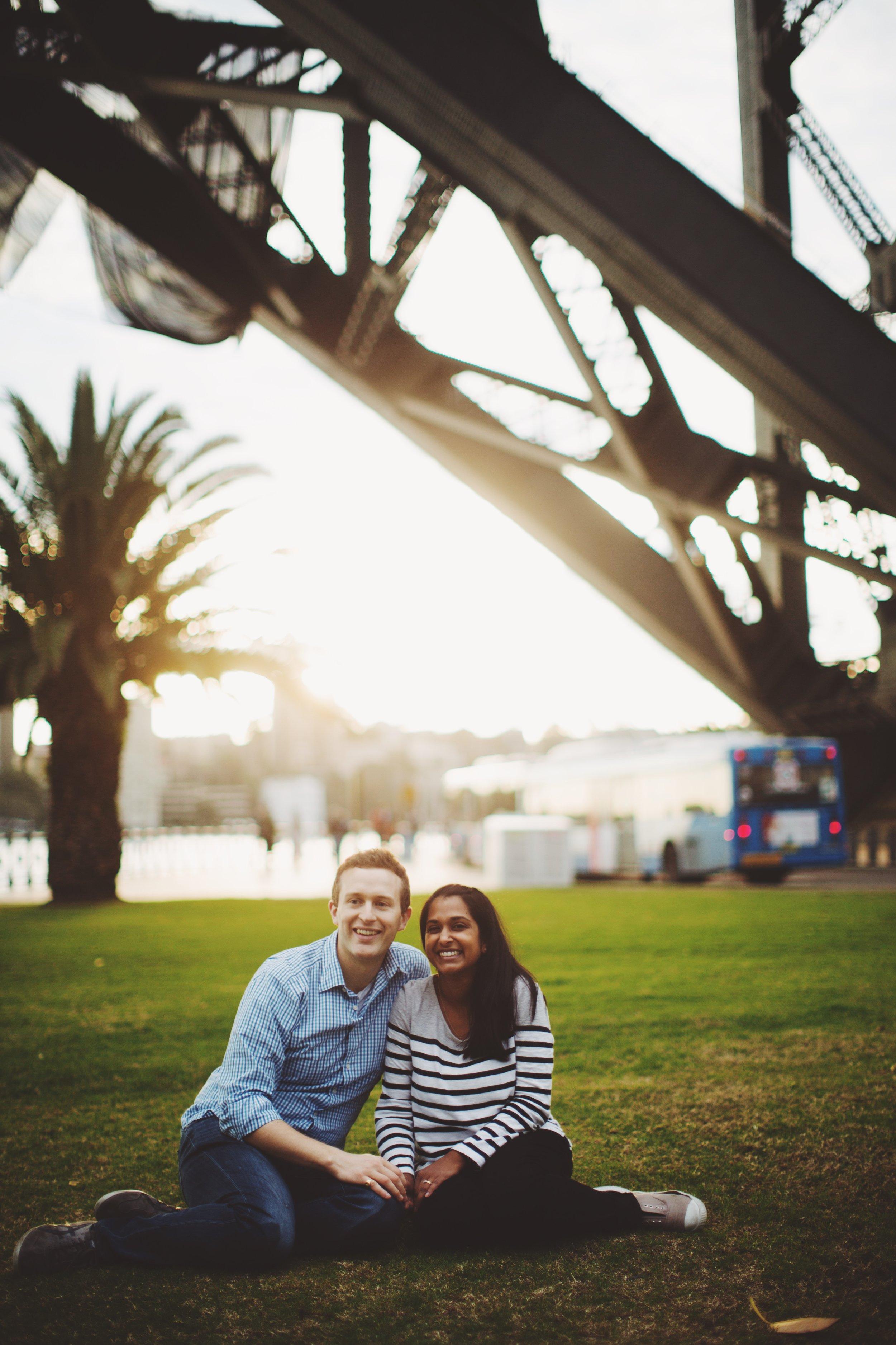 couple standing below Sydney Harbour Bridge