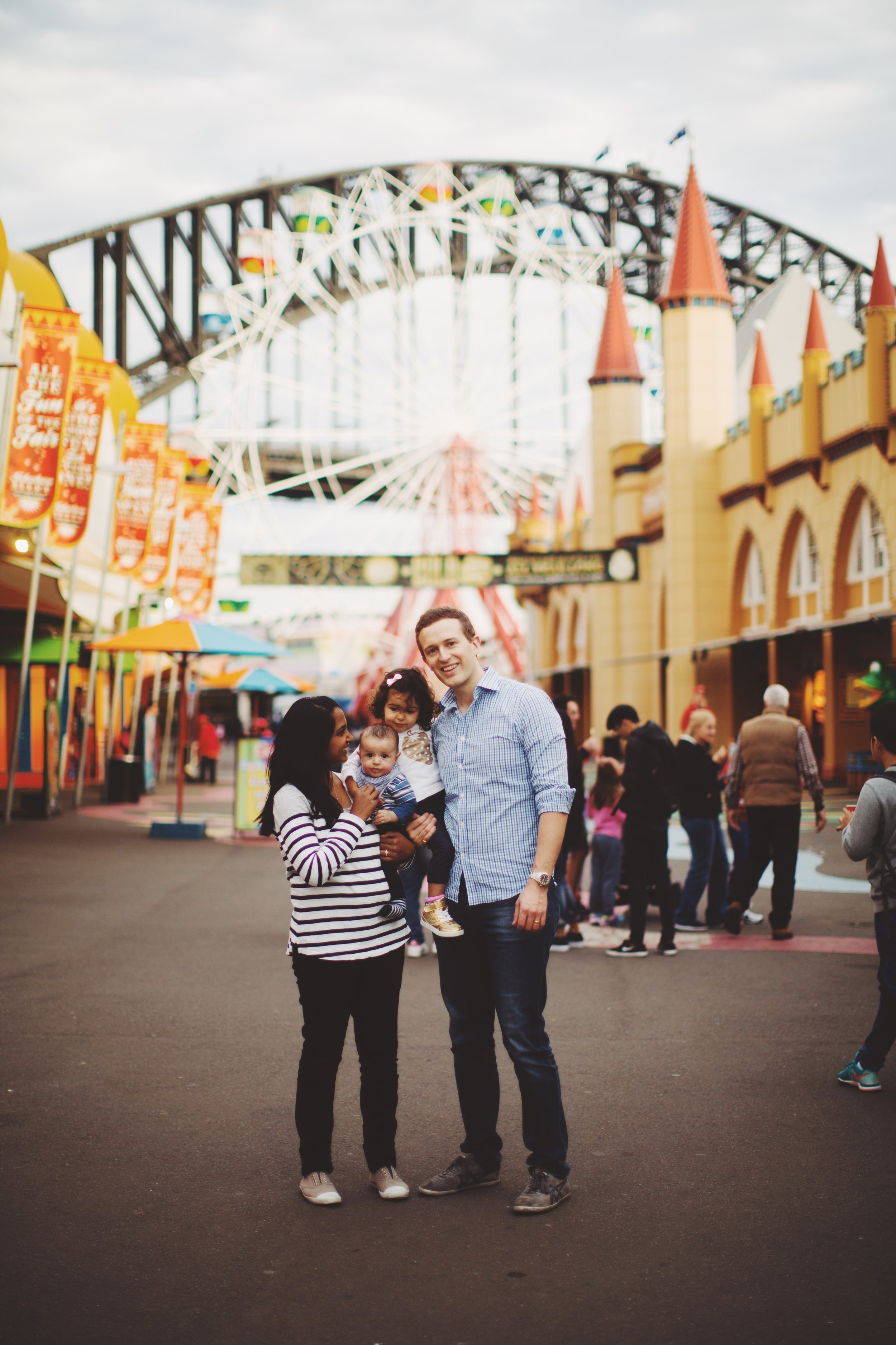 family of four stand at luna park in syndey