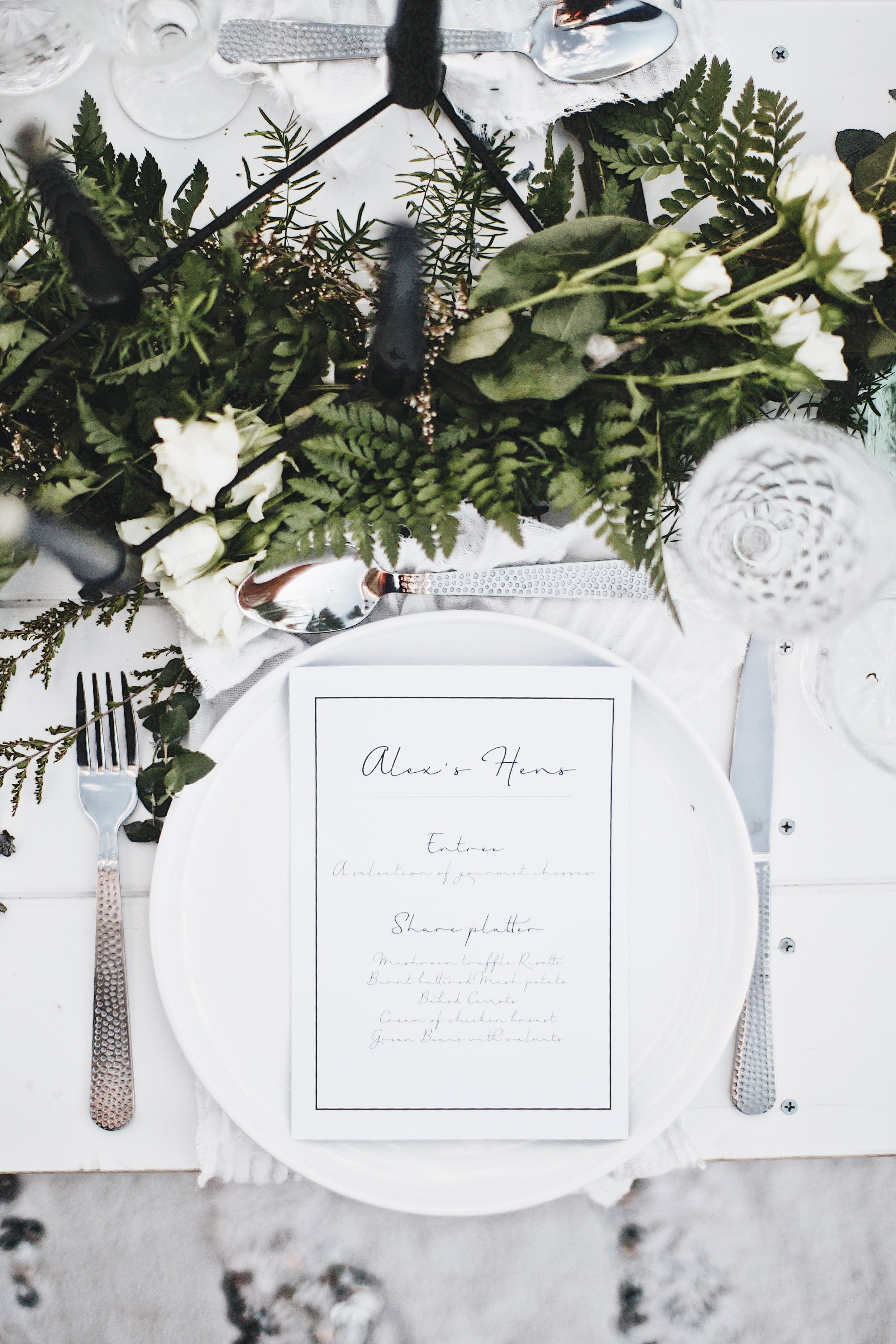 Table setting with white menu on plate and green florals