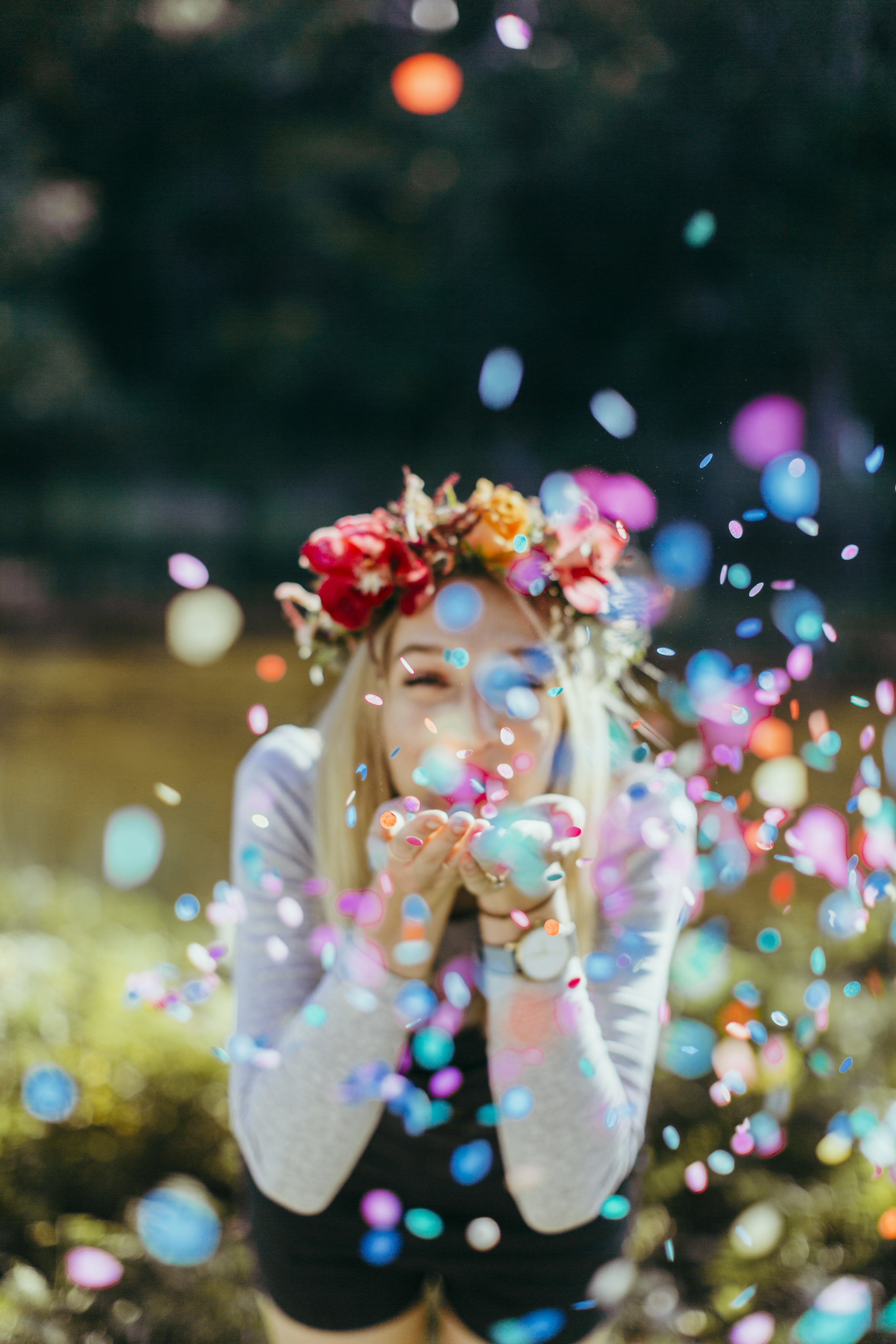 Woman wearing flower crown blowing brightly coloured confetti from her hands