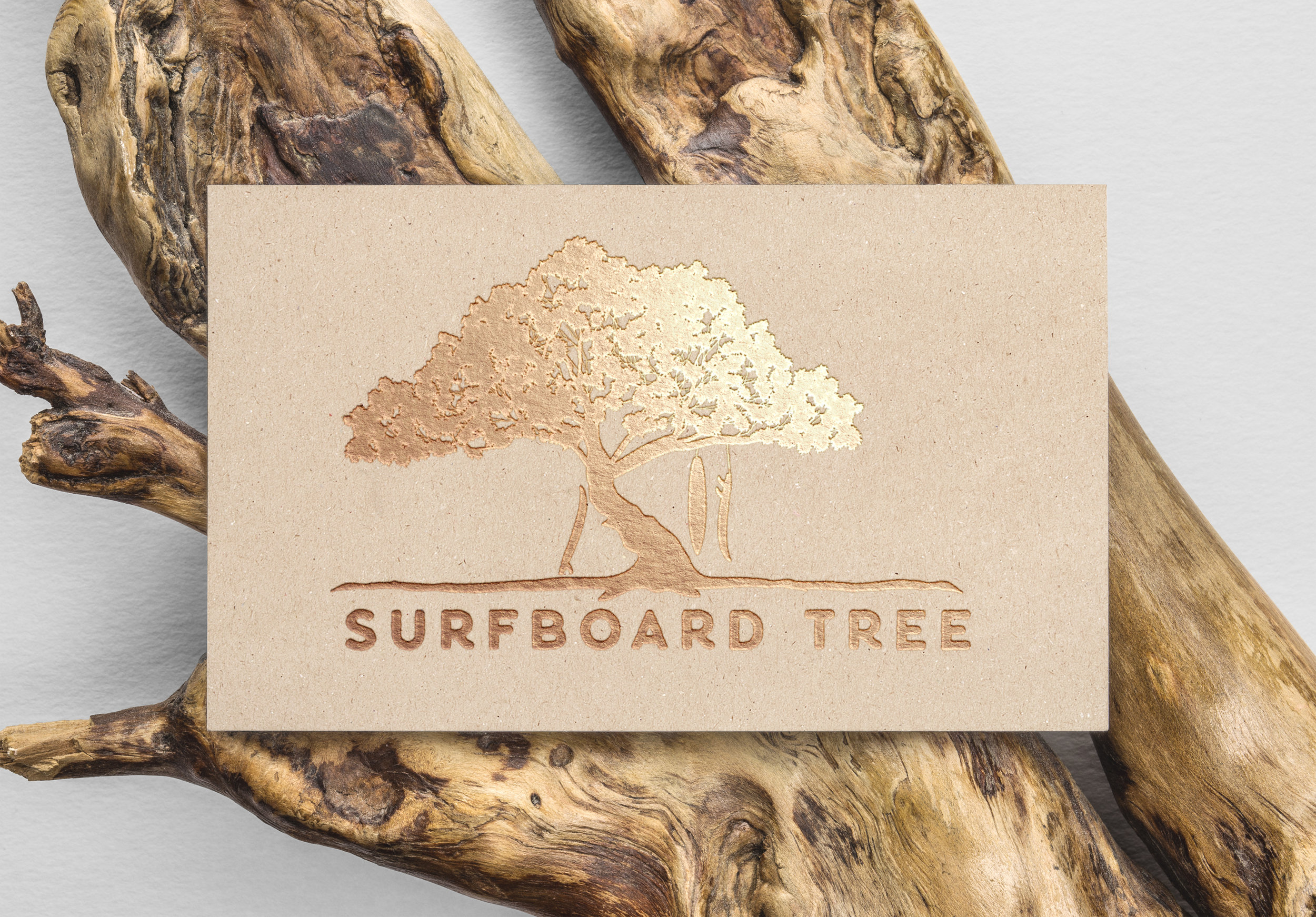 Surfboard tree business card on tan card with gold lettering and gold tree print above words