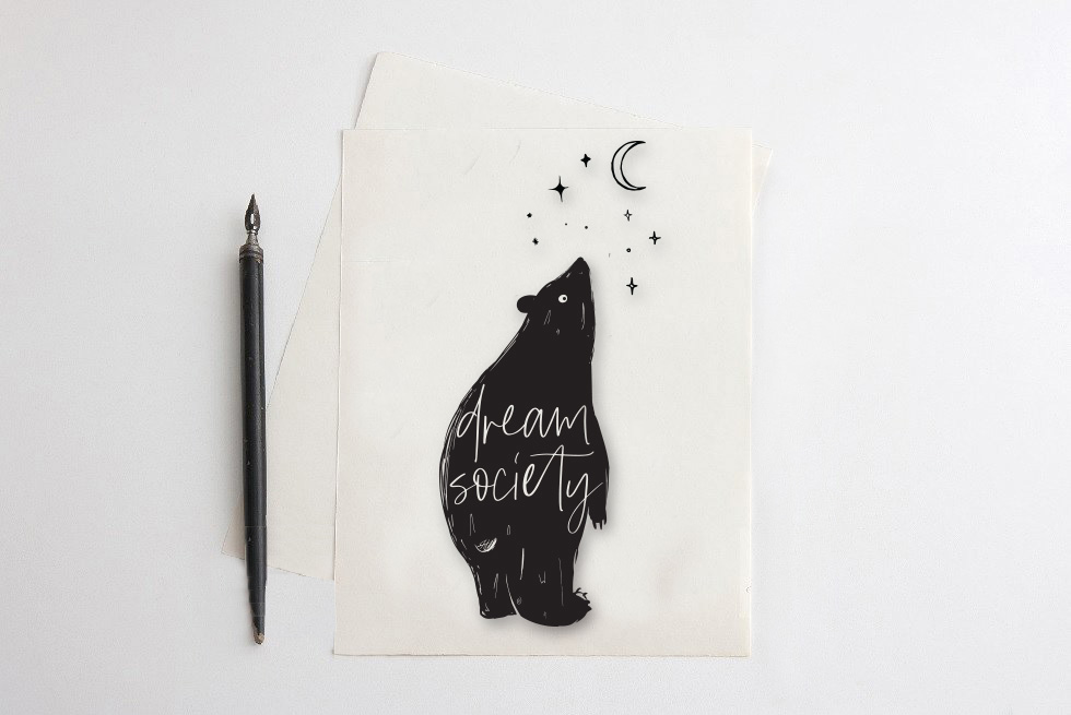 Drawing of a bear looking up at moon and stars with words printed on body