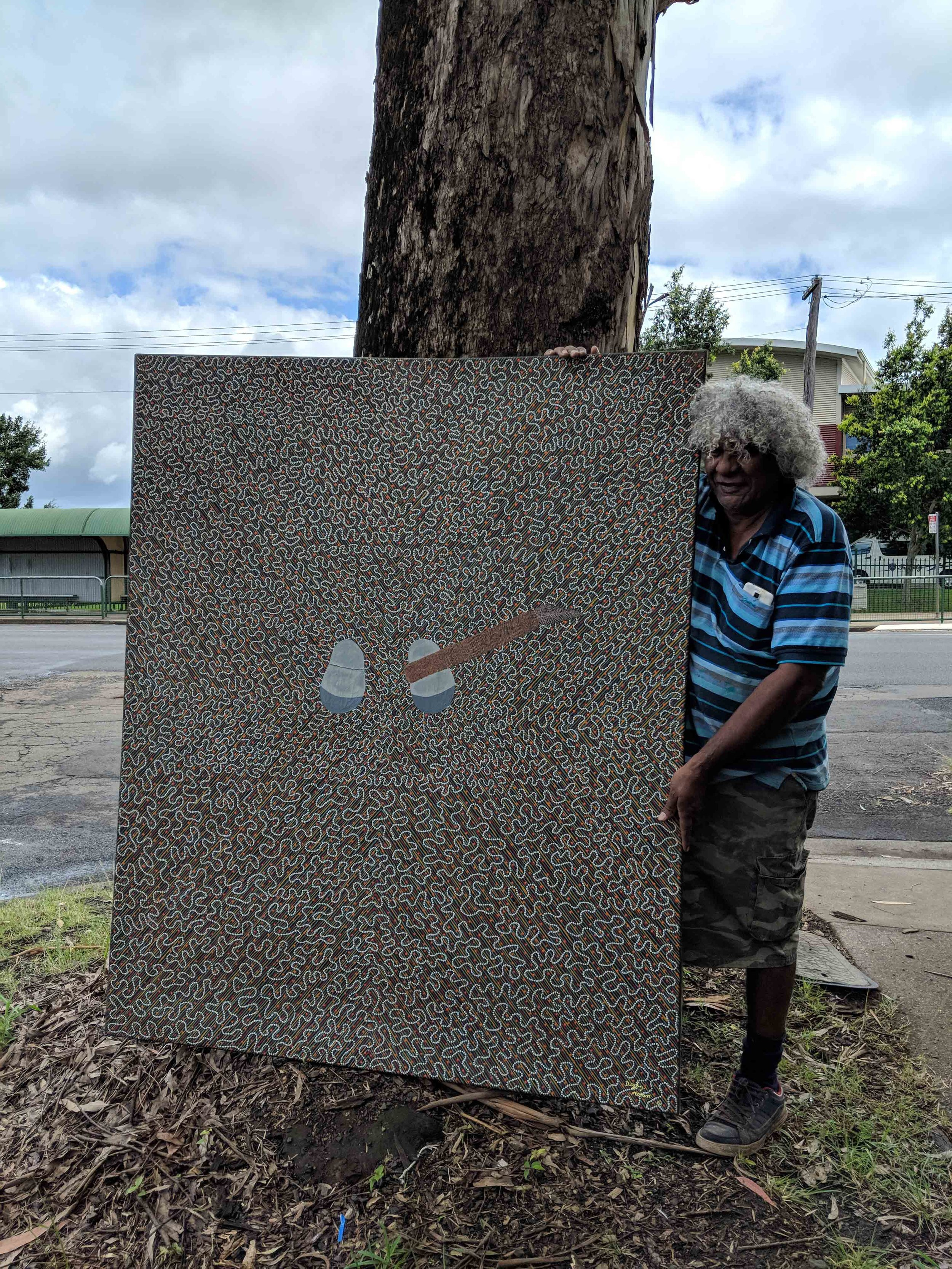 Digby Moran with his painting Bundjalung Stone Axe Gift of Margot Anthony AM, through the Tweed Regional Gallery Foundation Ltd., 2018 © The artist