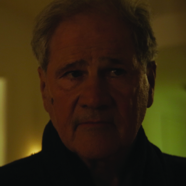 American Father Figure   He lives in the building and .under the thumb of his wife. As he is a mature and sensitive man Lil always knew he was the perfect emergency contact. The American Father Figure is played by Stephen Mendillo.  IMDB page