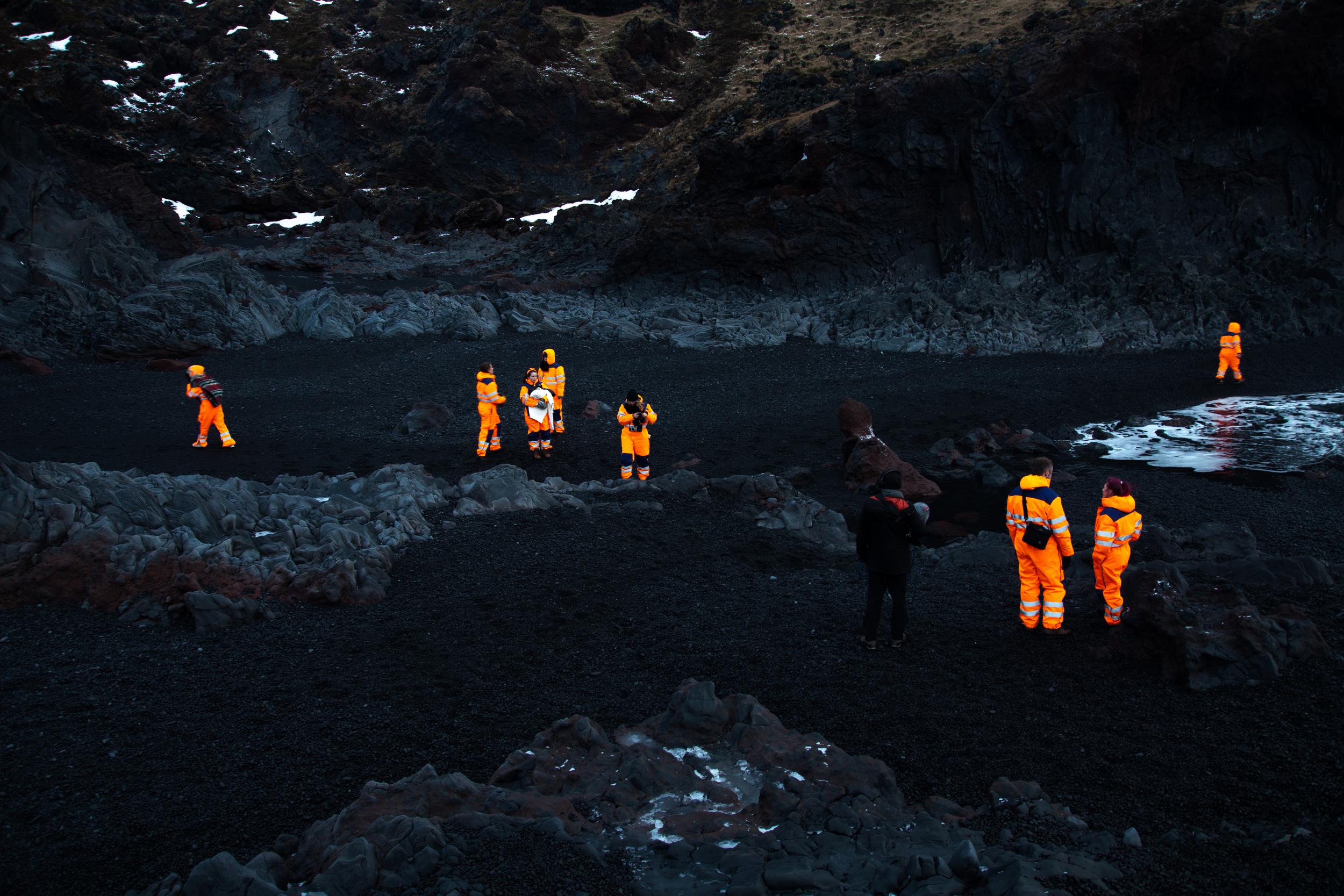 Orange suits on the black beach