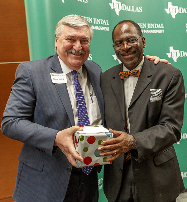Dr. Hasan Pirkul (left), dean of the Naveen Jindal School of Management, presents a gift to Dr. David L. Ford Jr. at a recent retirement celebration. After 42 years at UT Dallas, Ford will retire Aug. 31.
