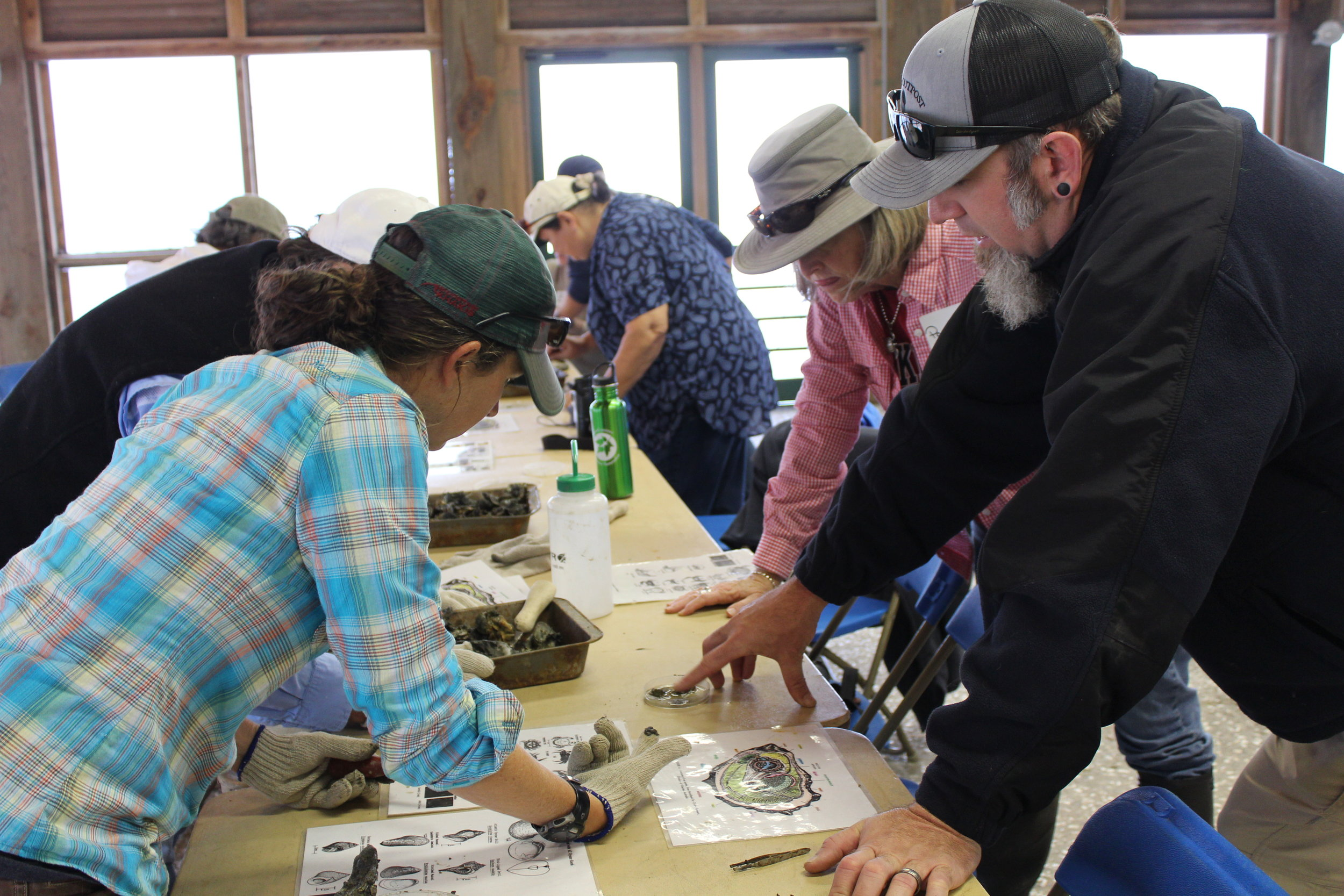 Biologist Michael Hodges (right) talks to workshop attendees dissecting a bag of oyster shells. (Photo: E. Weeks/SCDNR)