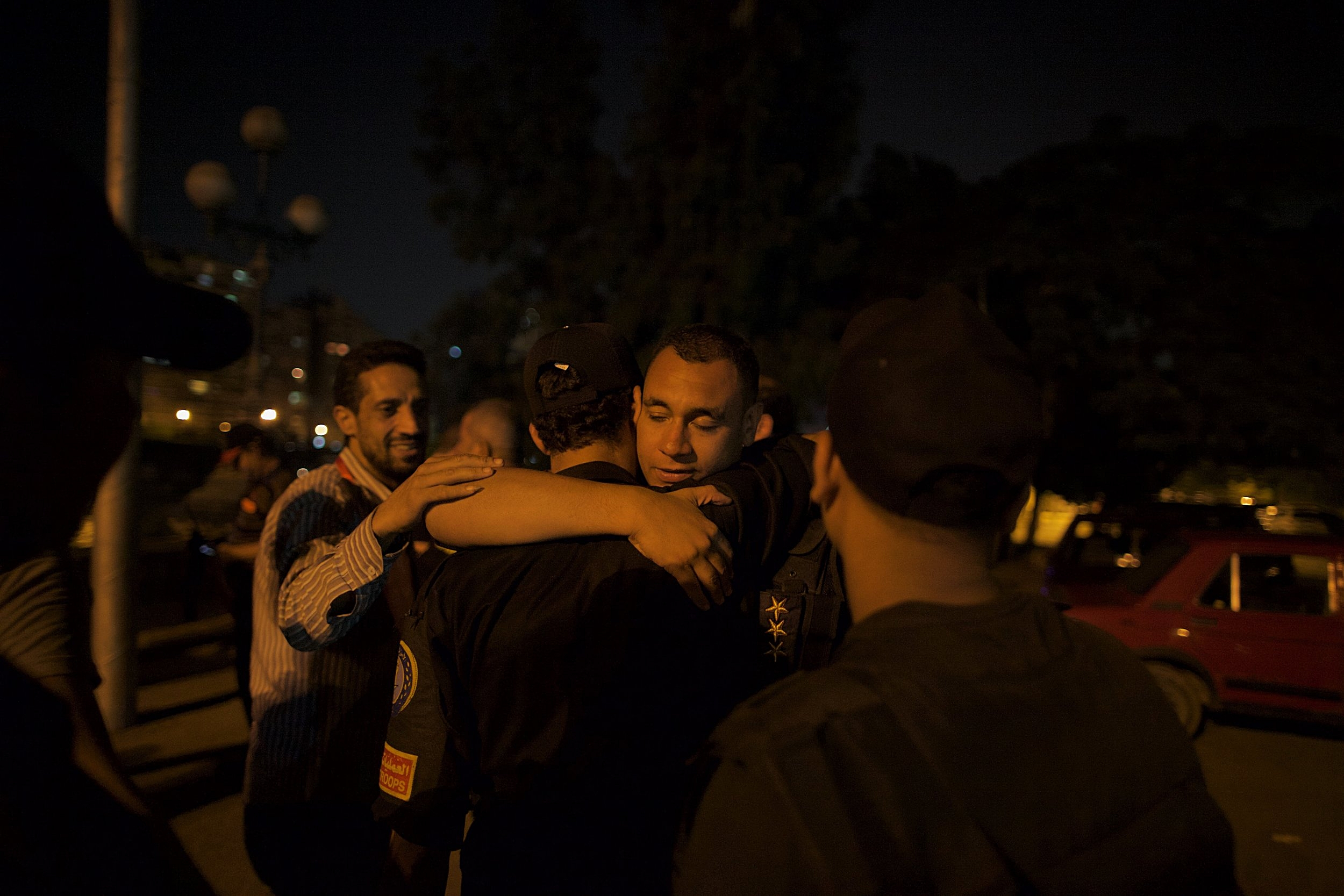Just outside Tahrir Square, members of Egyptian security services embrace moments after the military deposed Mohammed Morsi and installed Gen. Abdel Fattah el-Sisi as president.