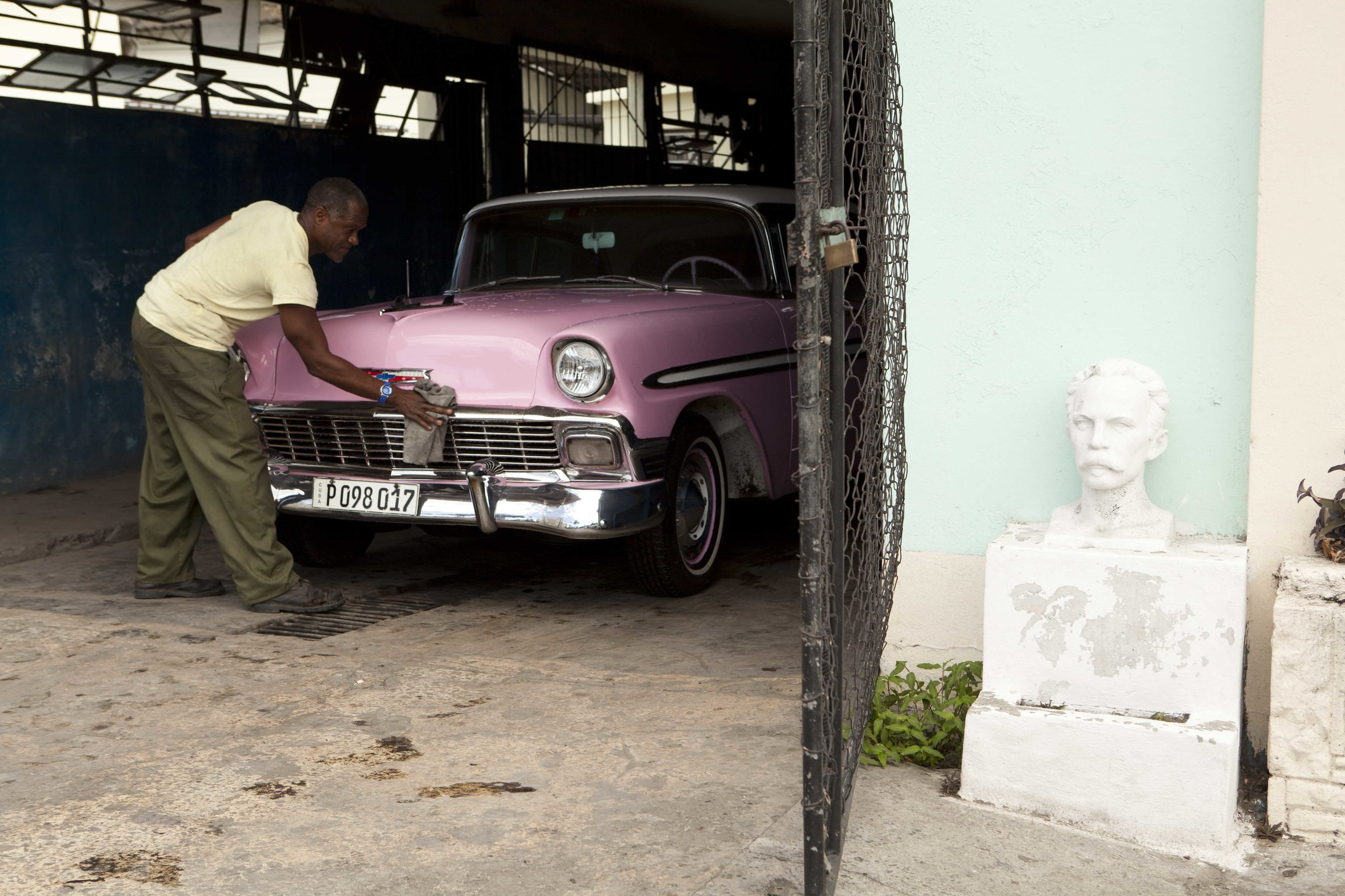 by Justin Lanier  A man cleaning a classic Chevy in Miramar, Havana  2015