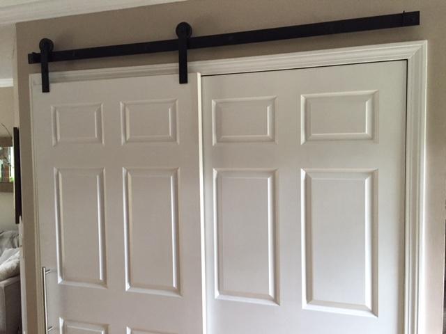 Barn door hardware by  Rustica Hardware  holds original closet doors.