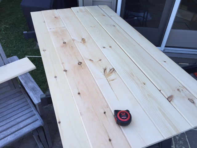 Several planks of shiplap siding along with some other pieces laid out before assembly.